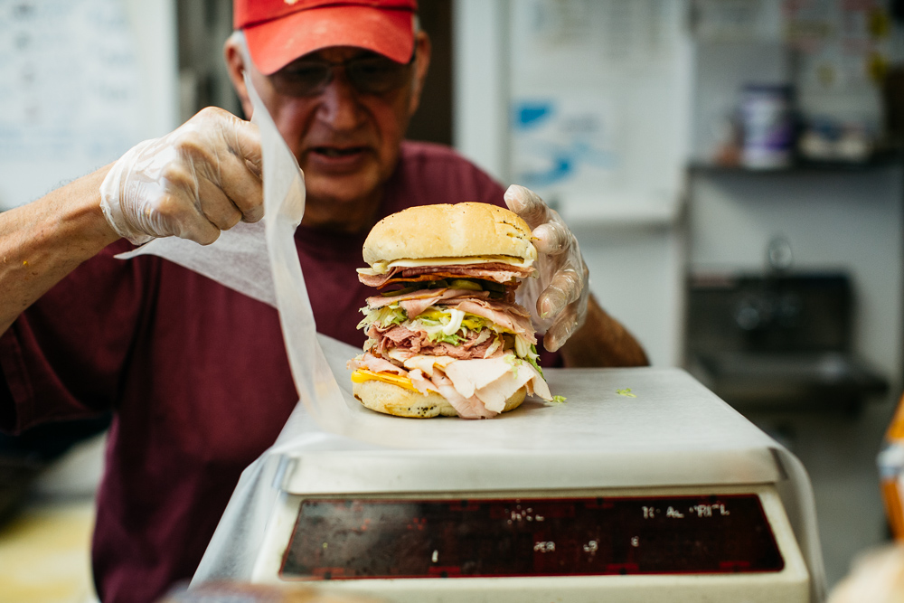 Ernie in a red hat weighing a really tall sandwich and wrapping it in wax paper.