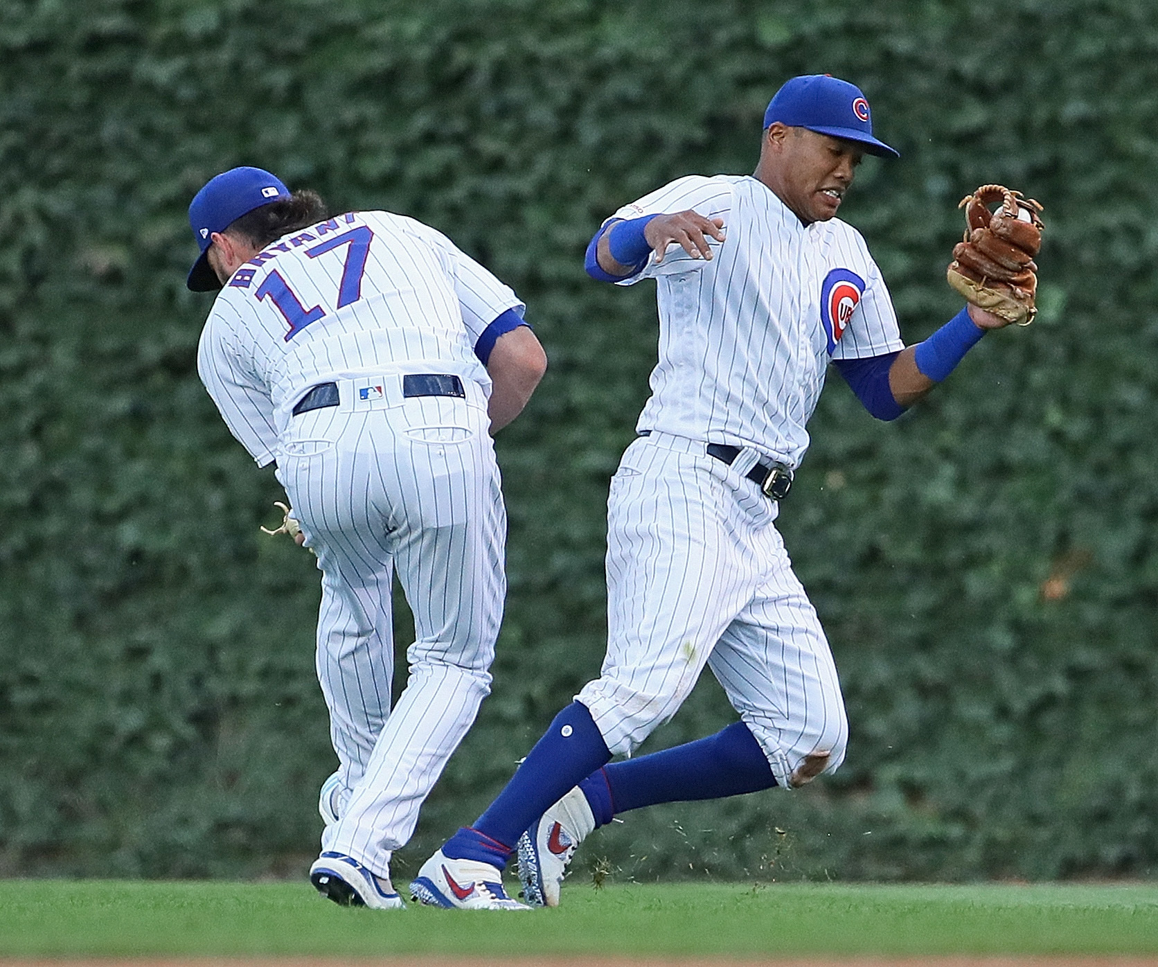 Kris Bryant #17 (L) and Addison Russell #27 of the Chicago Cubs have a minor collision as Russell makes a catch in the 1st inning against the Cincinnati Reds at Wrigley Field on July 15, 2019 in Chicago, Illinois.