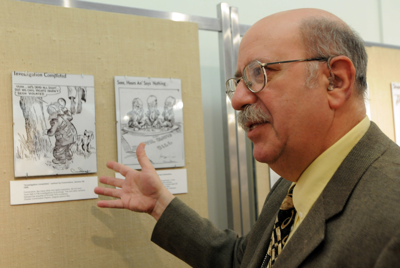 Michael Flug with works by Chicago Defender cartoonist Chester Commodore at the Carter G. Woodson Regional Library in May 2008.