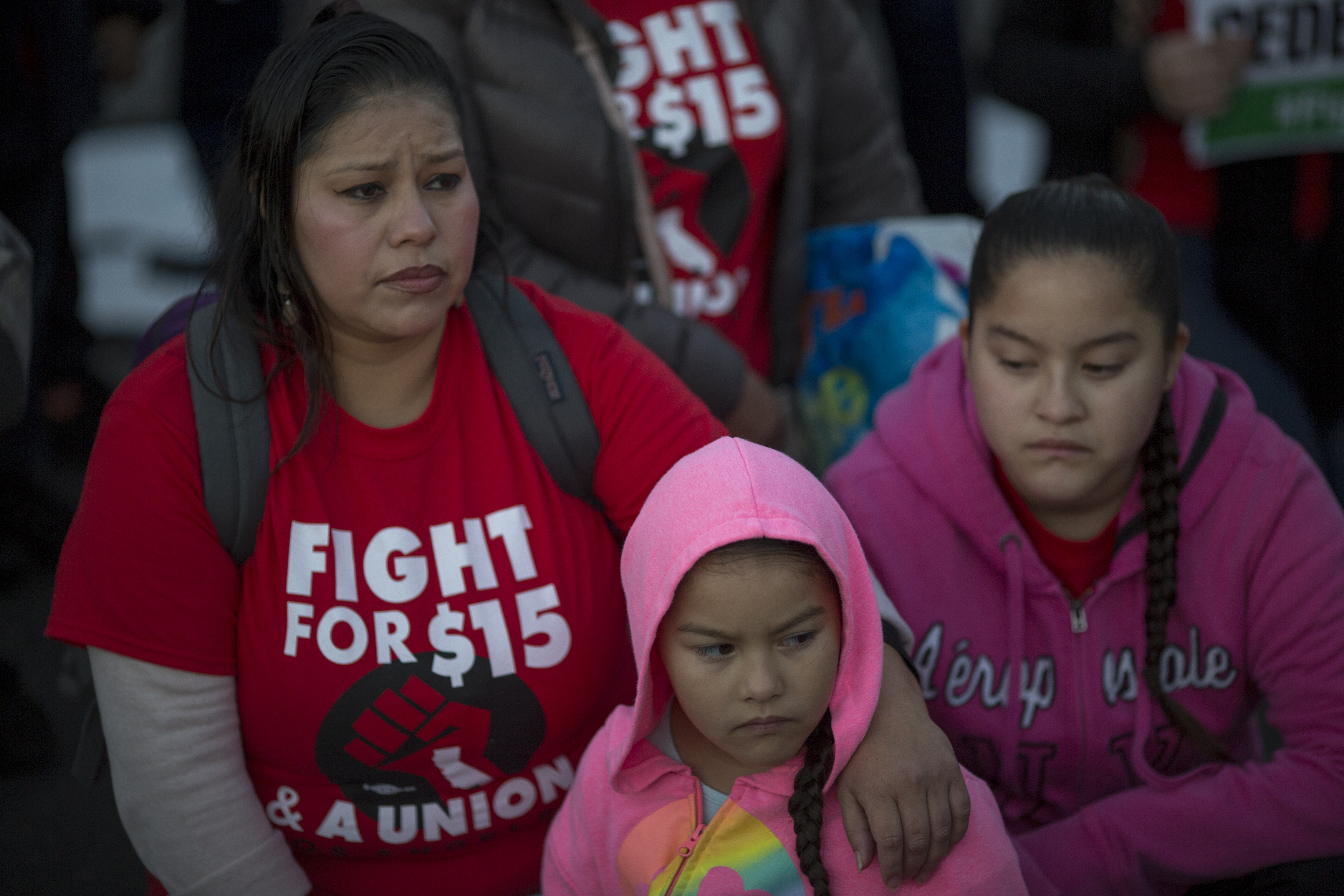 "A protestor wears a shirt that reads ""Fight for $15"" while at a rally with her two daughters."