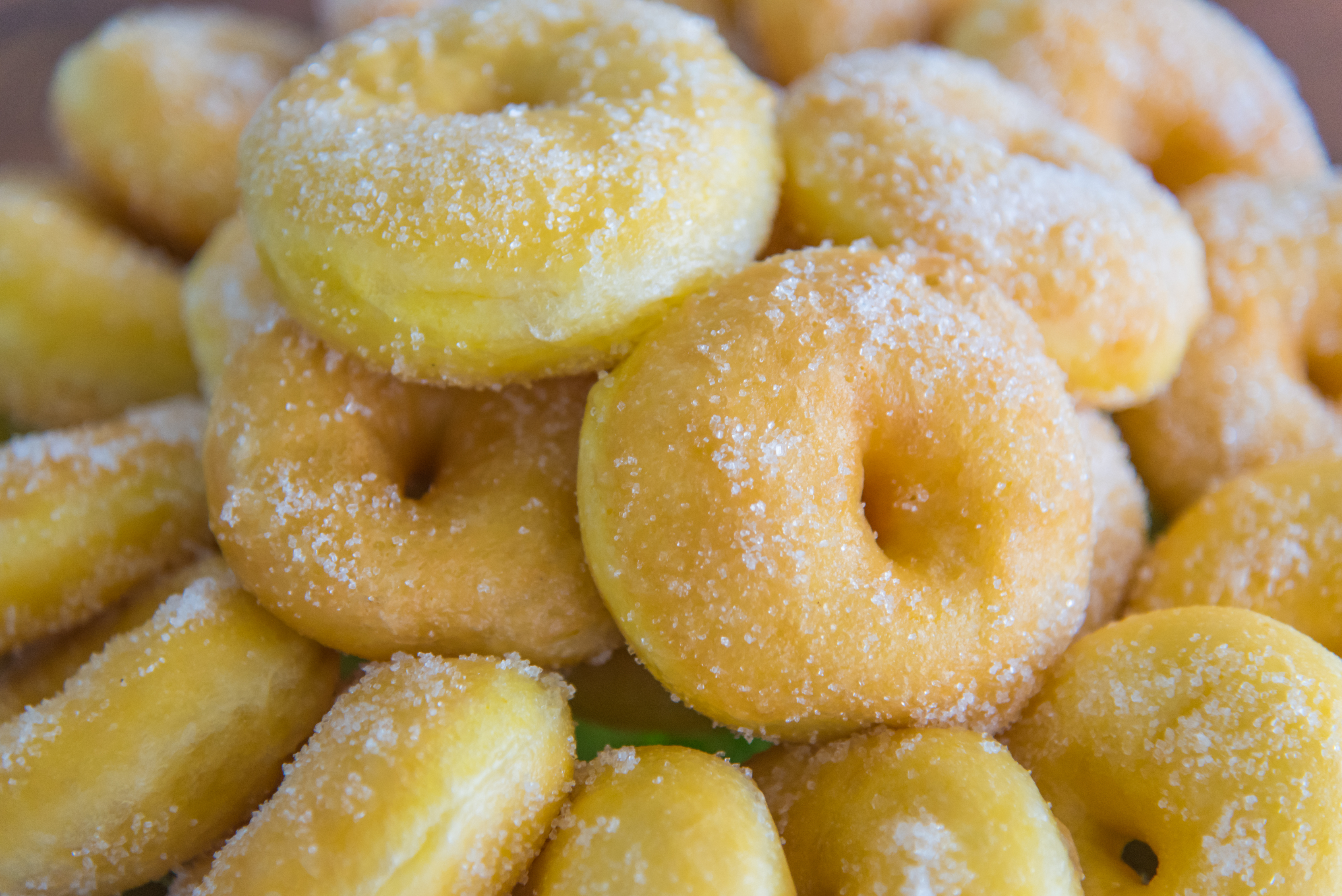 a pile of mini doughnuts tossed in sugar