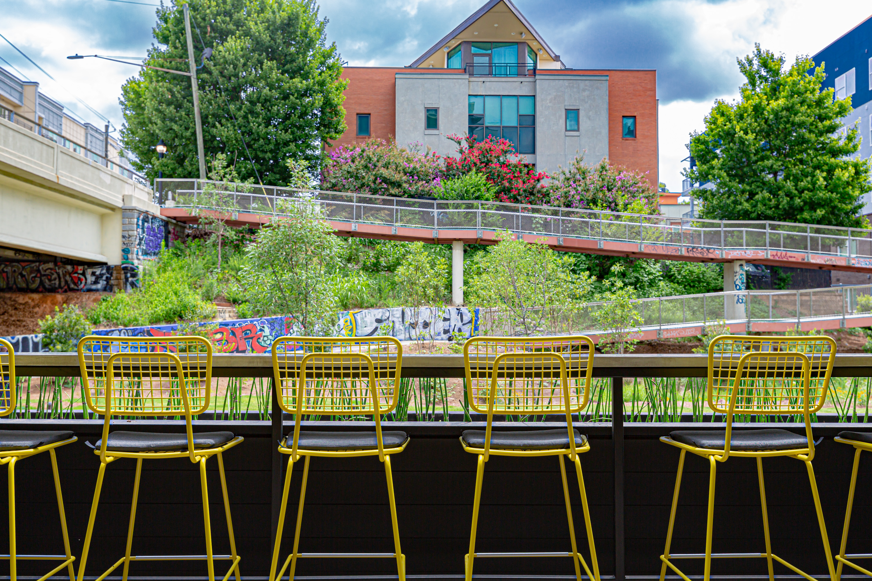 Four yellow bar chairs at the rail on the covered, front patio overlooking the Eastside Beltline trail at the Edgewood Avenue bridge