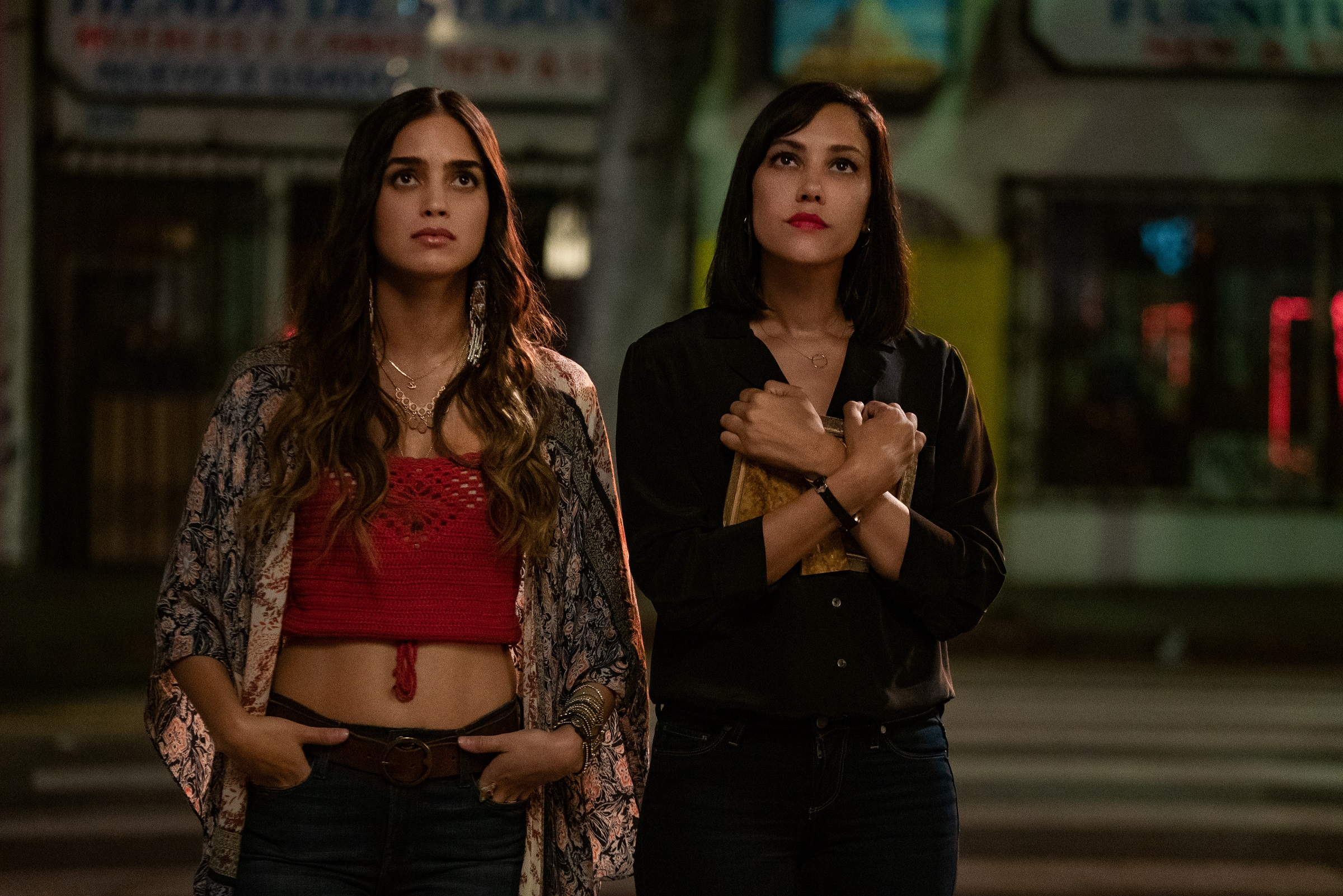 Lyn, played by Melissa Barrera, and Emma, played by Mishel Prade, stand outside the bar owned by their mother in the Starz show Vida.