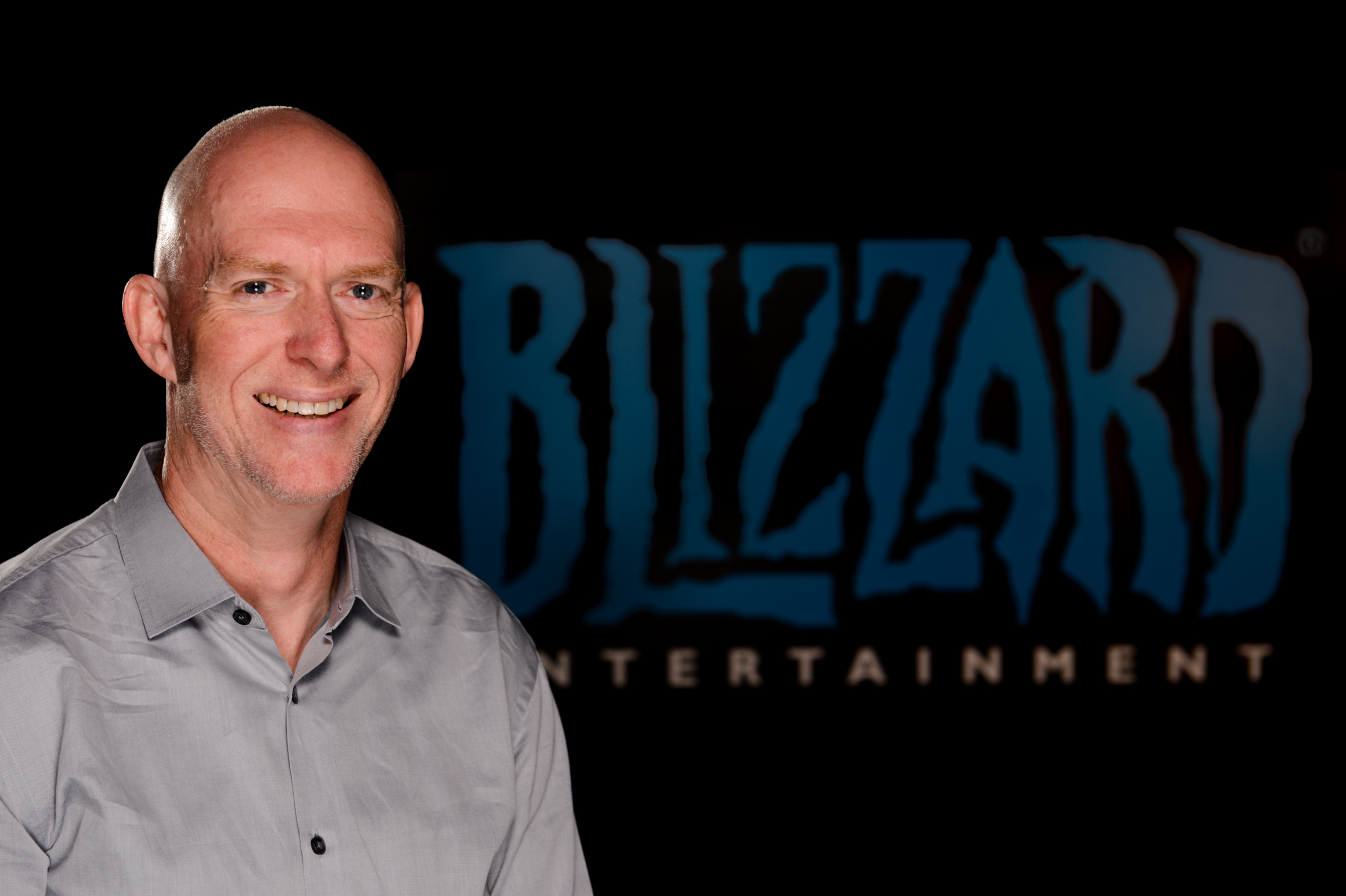 Photo of Blizzard co-founder Frank Pearce sitting in front of a darkened company logo