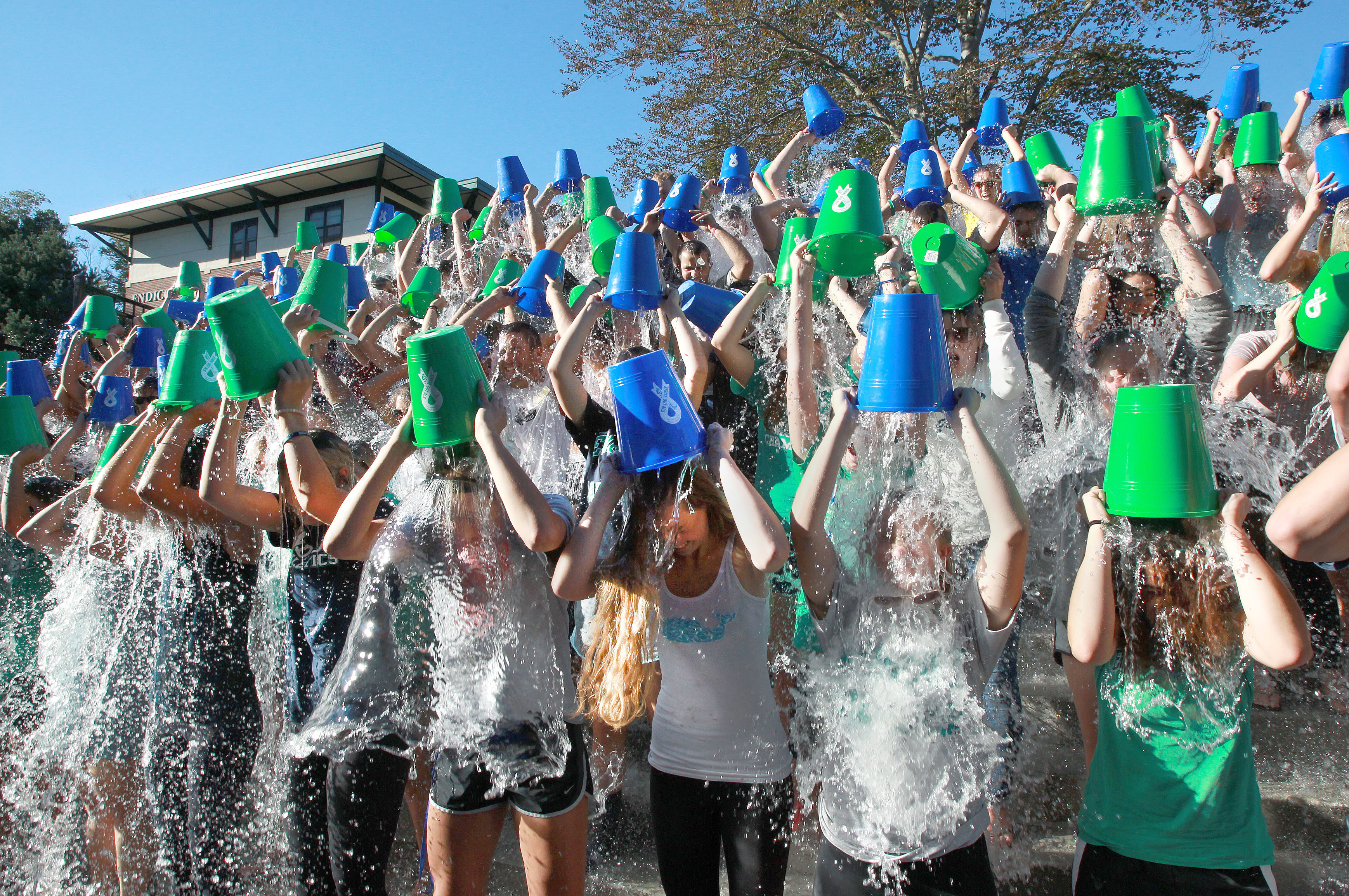 Students dump colorful buckets of ice water on their heads.