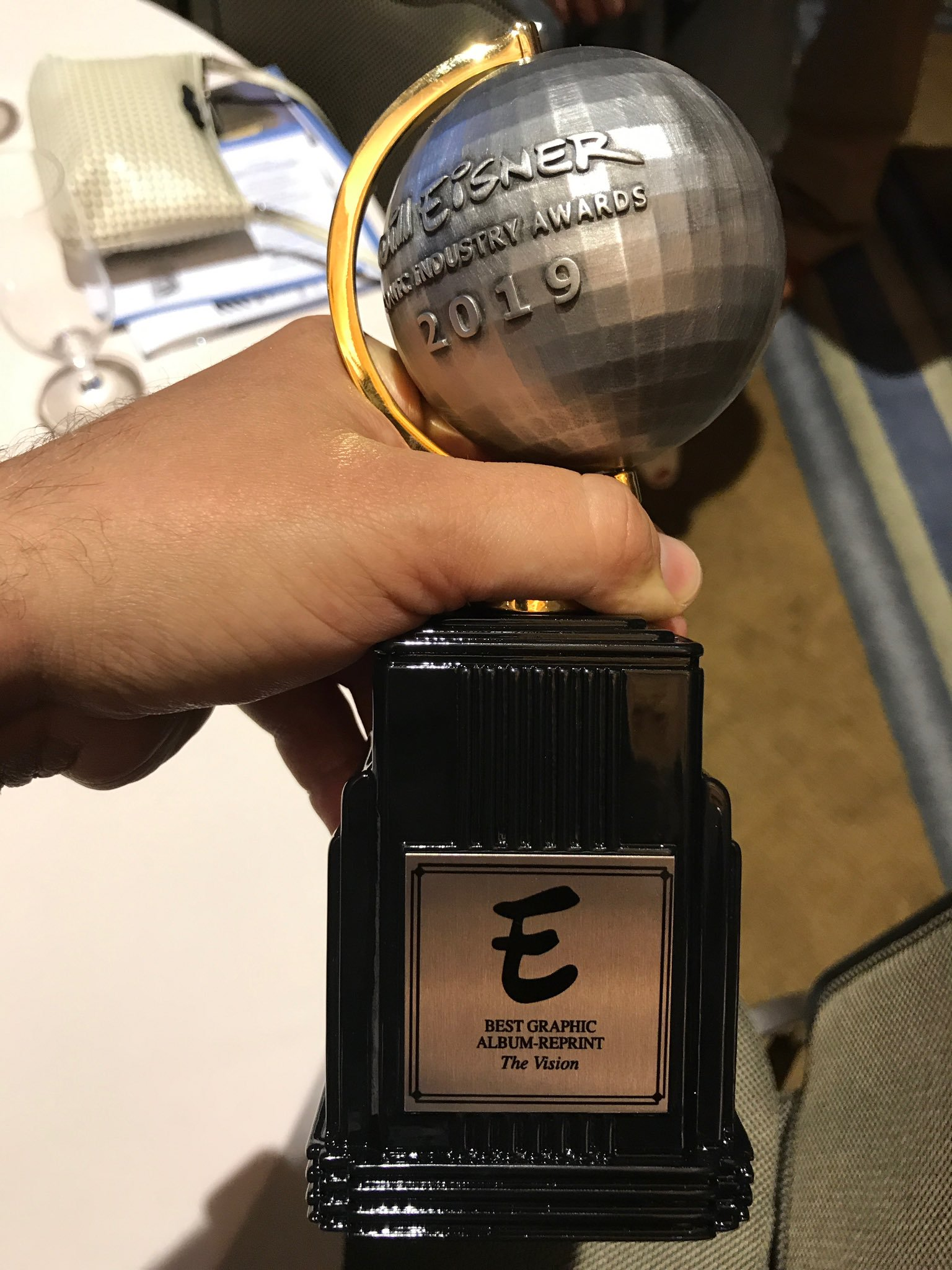 Closeup of a hand holding the 2019 Eisner Award for Best Graphic Album—Reprint (winner: The Vision)