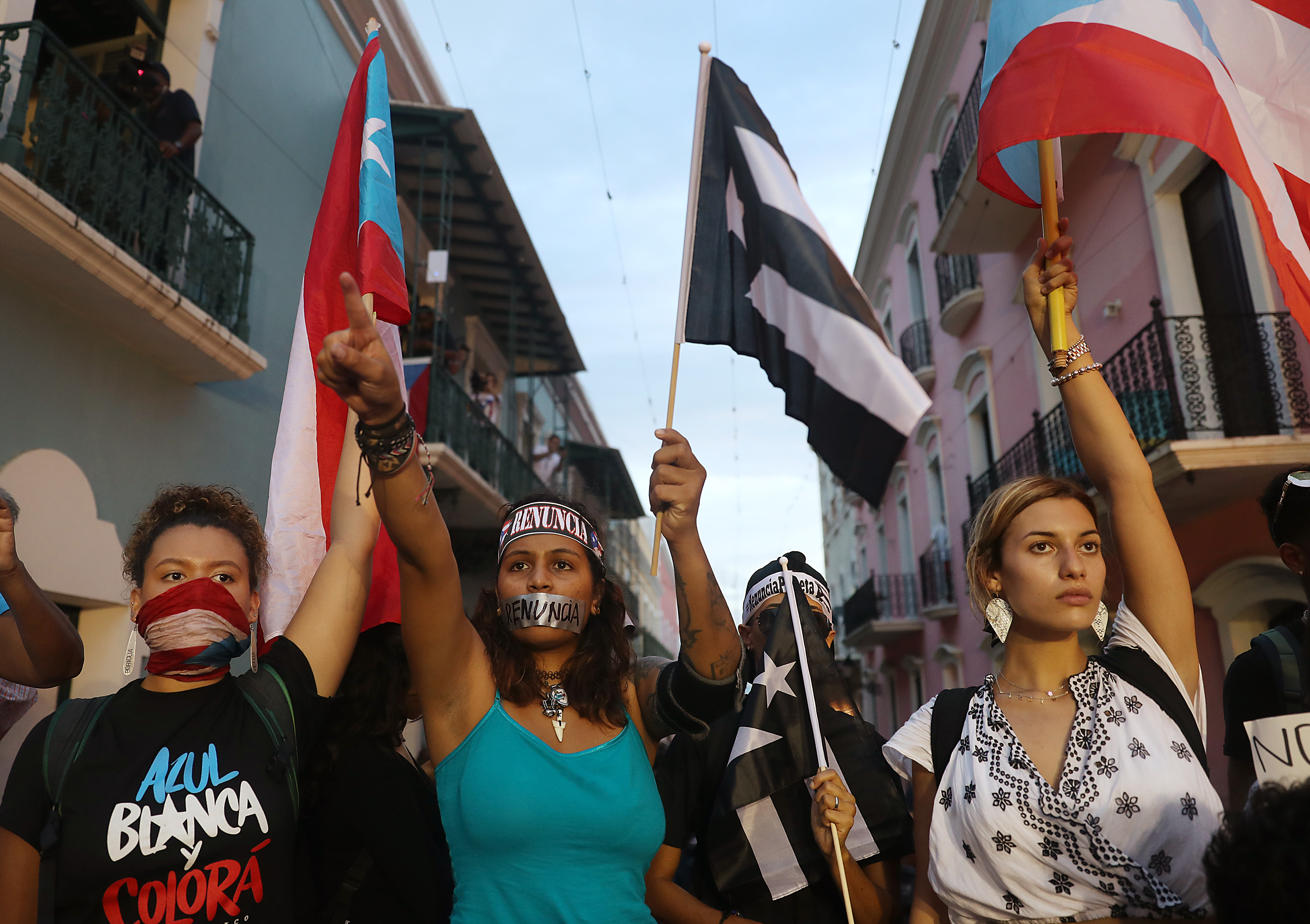 Three woman — two of whom have their mouths covered with tape or a scarf — wave Puerto Rican flags at a protest calling for the resignation of Gov. Ricardo Rosselló.