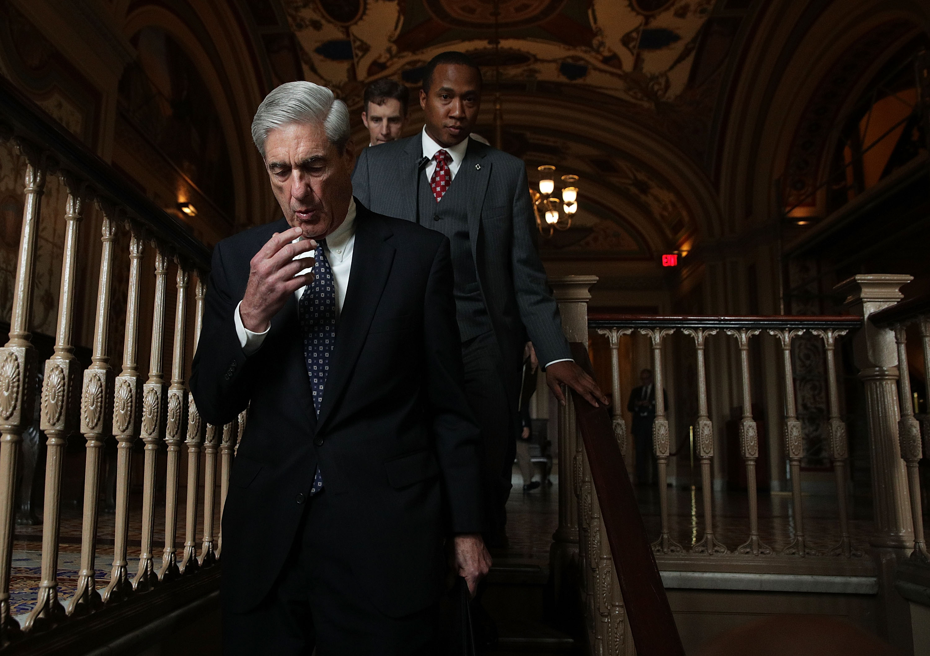 Special counsel Robert Mueller walks down a dark staircase at the US Capitol.