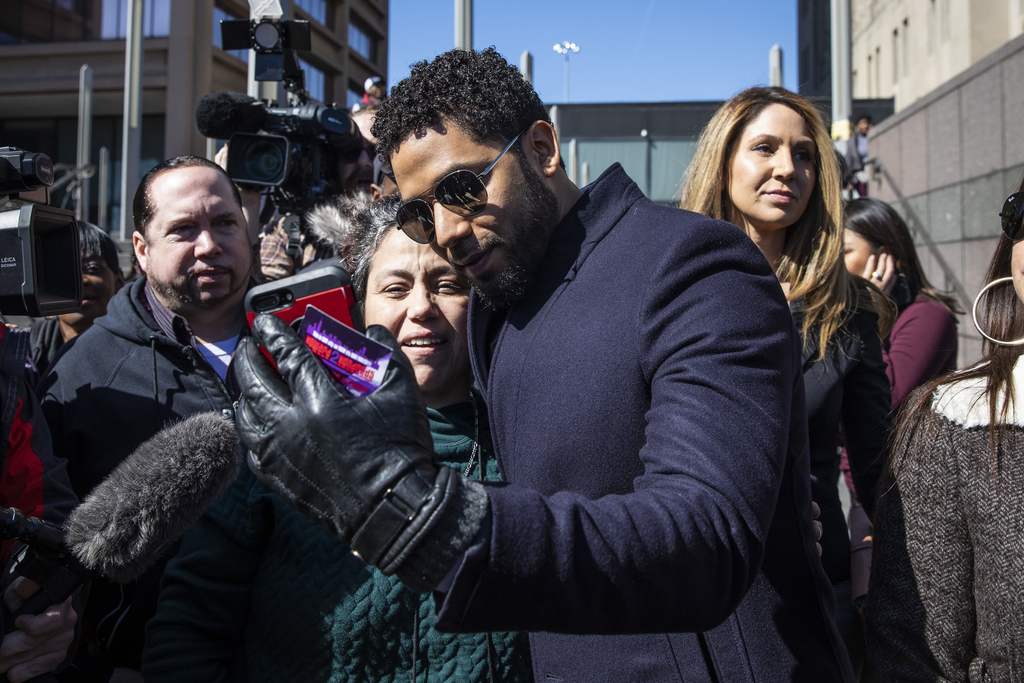 Jussie Smollett takes a selfie with a supporter as he leaves the Leighton Criminal Courthouse.