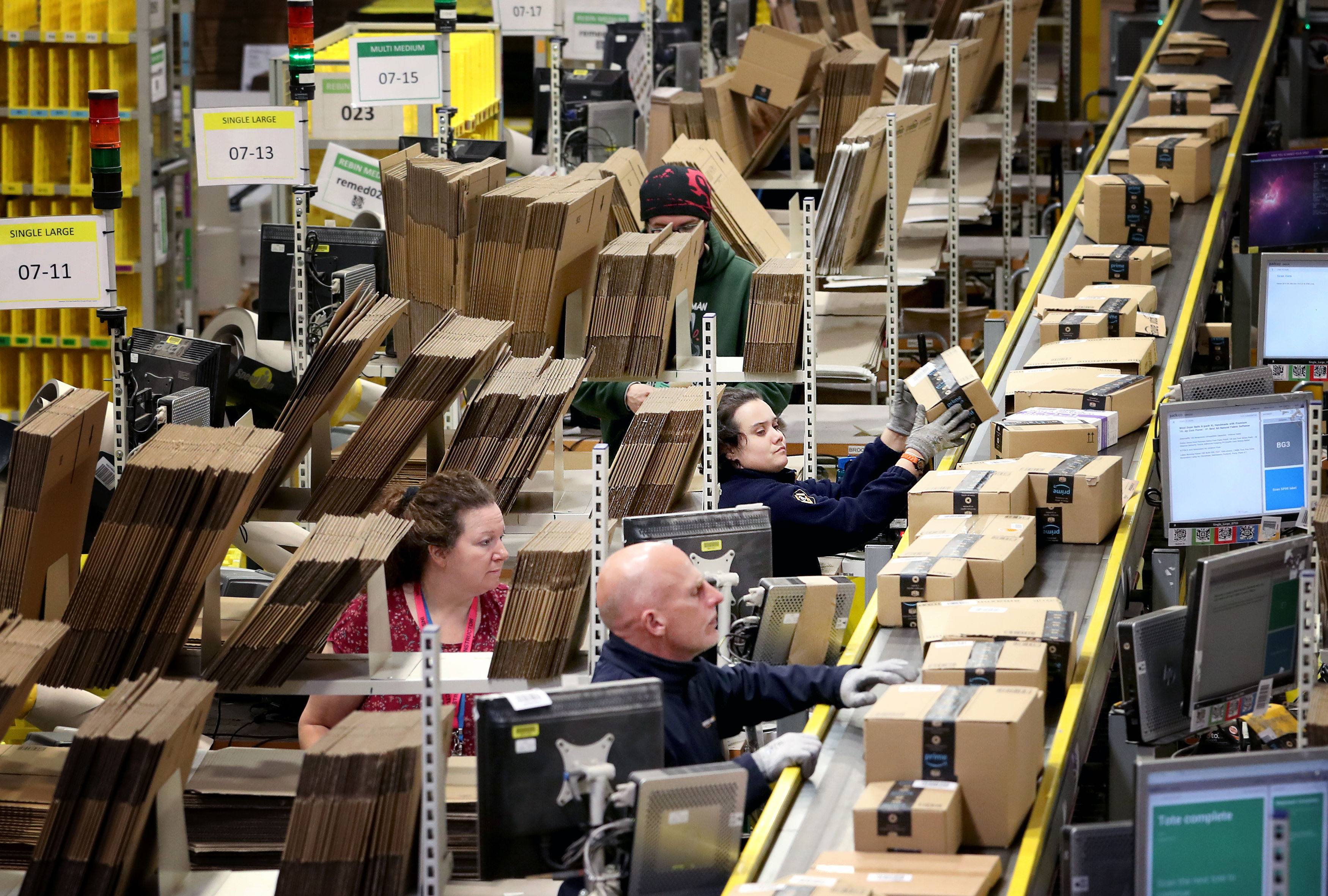 Workers in an Amazon fulfillment center loading cardboard boxes onto a conveyor belt.