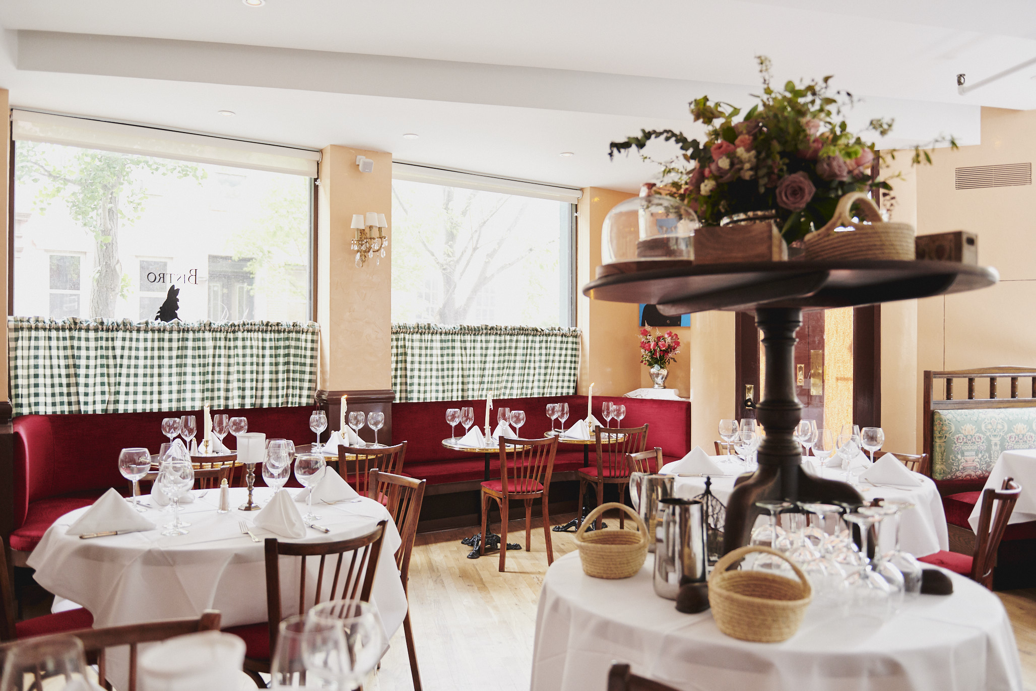 Bistro Pierre Lapin's dining room with white tablecloths and checkered windows