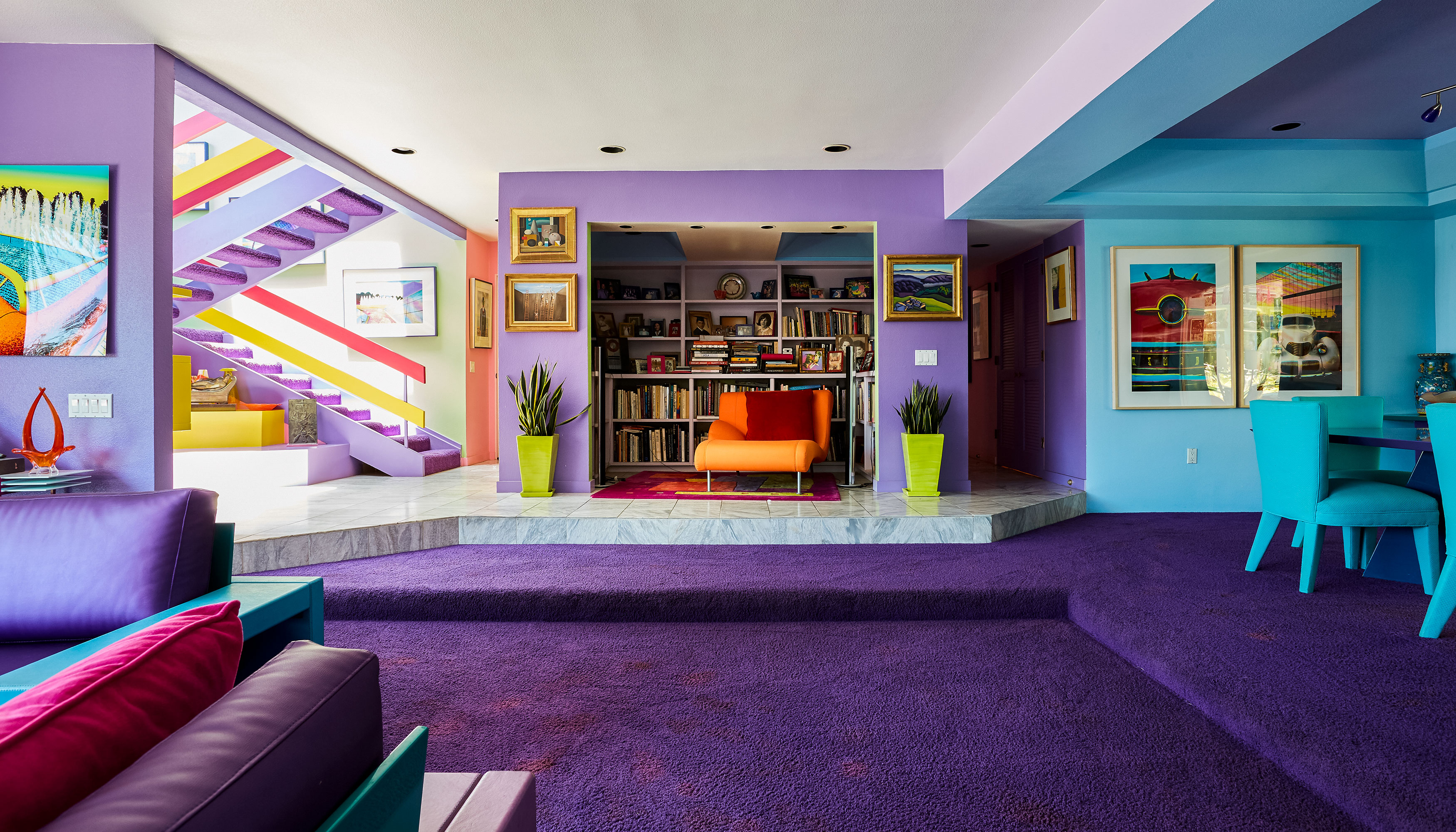 Jane Gottlieb's colorful living room with purple carpet, purple walls, and colorful artwork on the walls