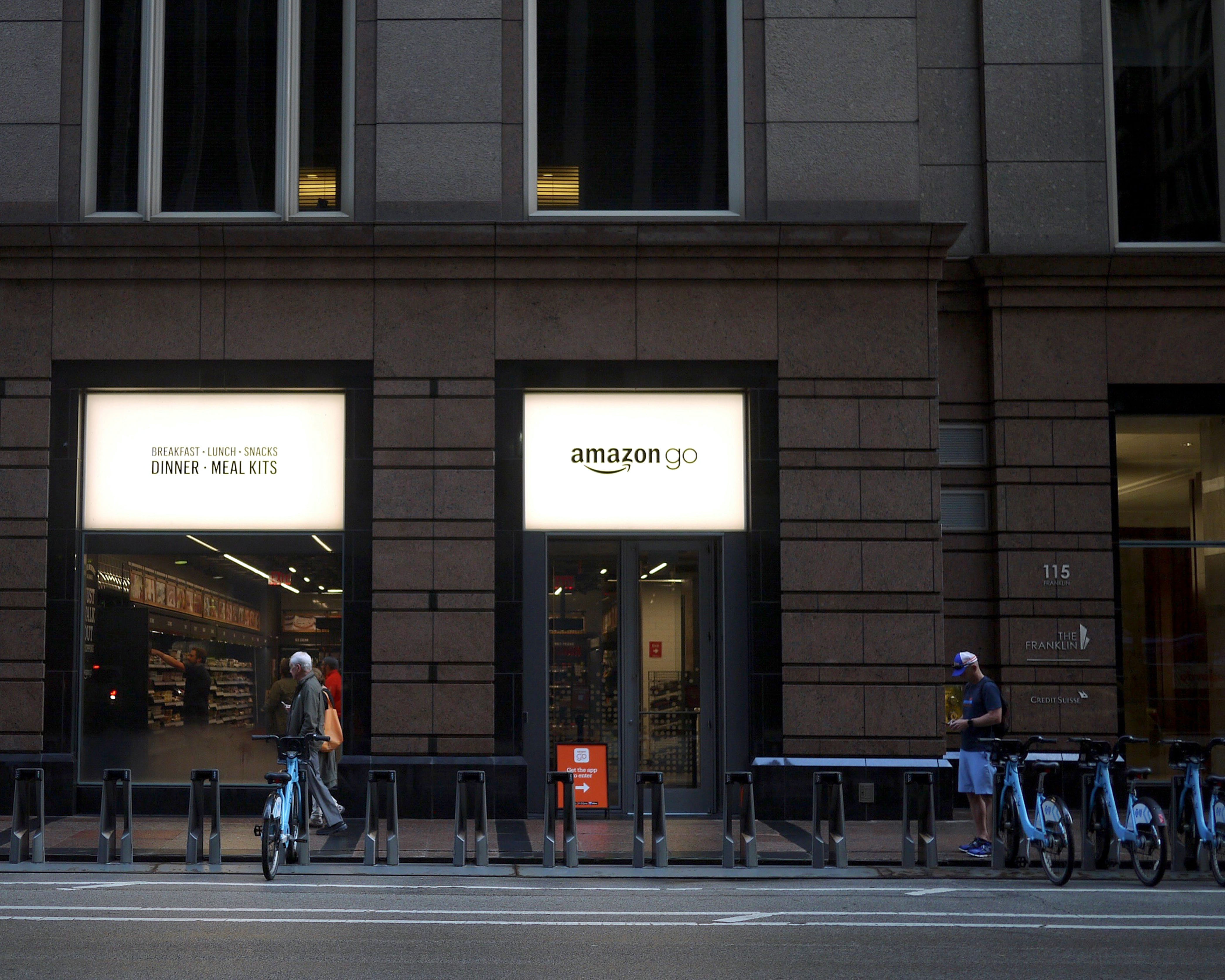 A photo of an exterior downtown office building in Chicago. A blue Divvy bike station is in front of two windows with a white Amazon Go sign.