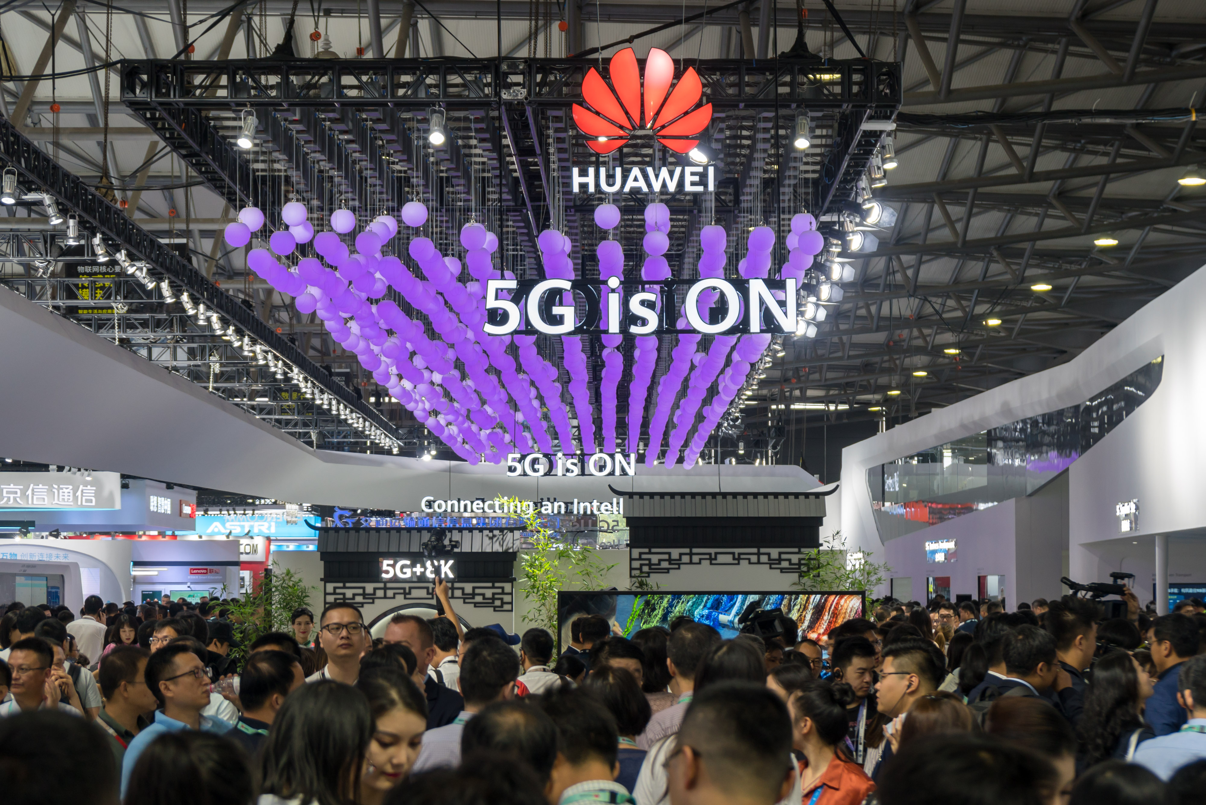 "A crowd of attendees at the Mobile World Congress under a sign reading ""Huawei: 5G is ON."""