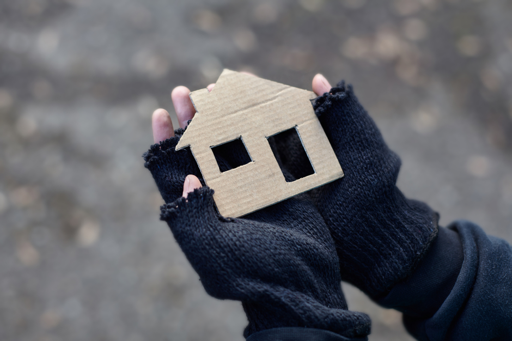 A pair of hands holding a cardboard cutout of a house.