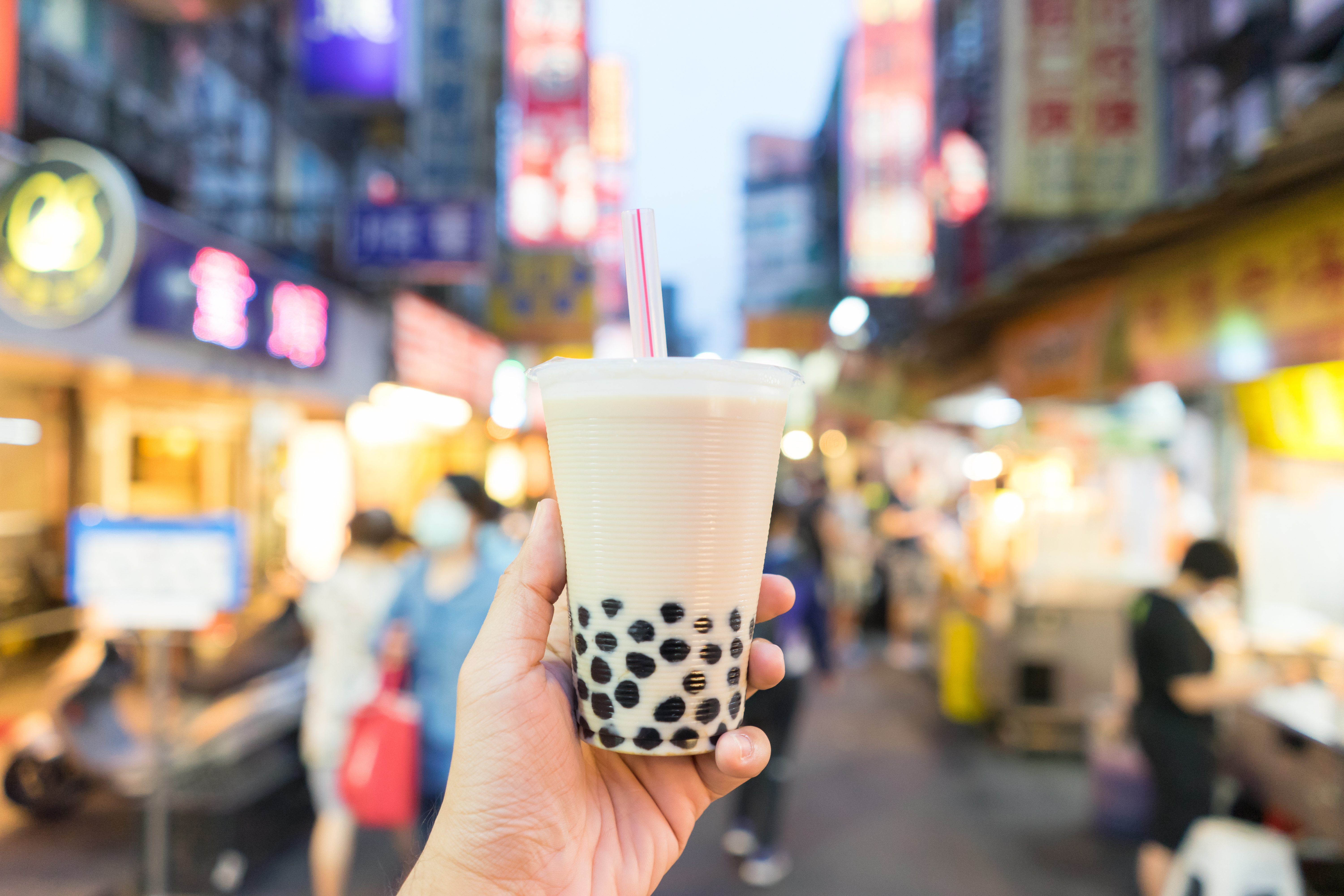 A hand holding up bubble tea; in the background, the lights of a Taiwanese night market.
