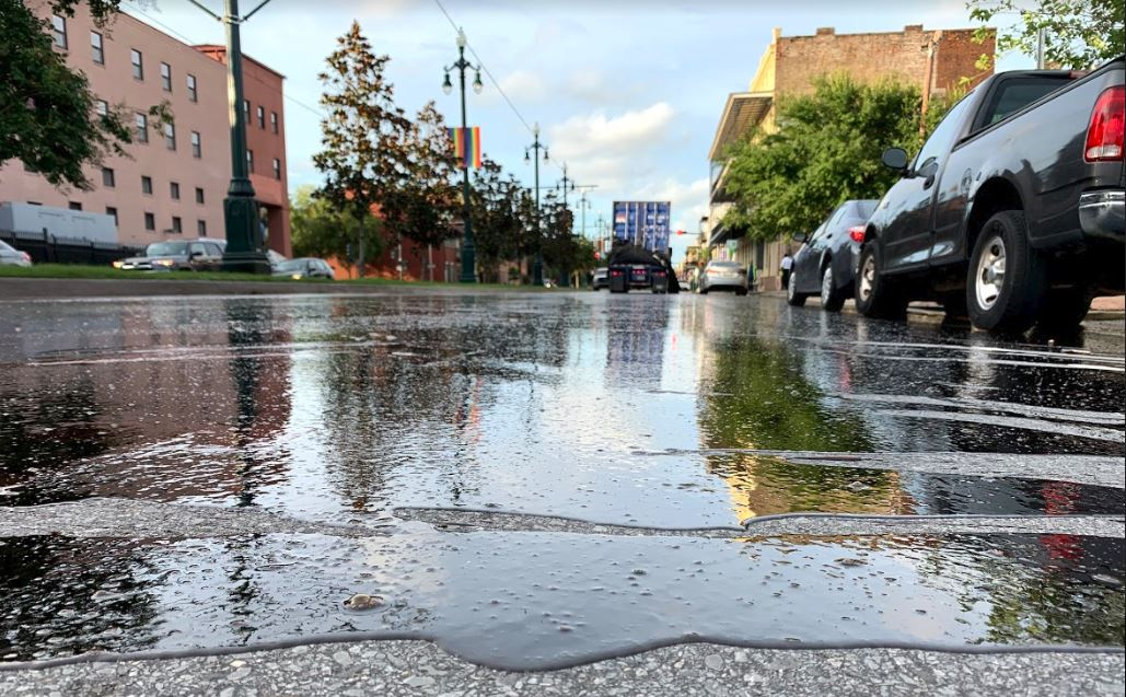 Syrup covers a stretch of Rampart Street between streetcar tracks on the neutral ground and cars parked on the right side of the street