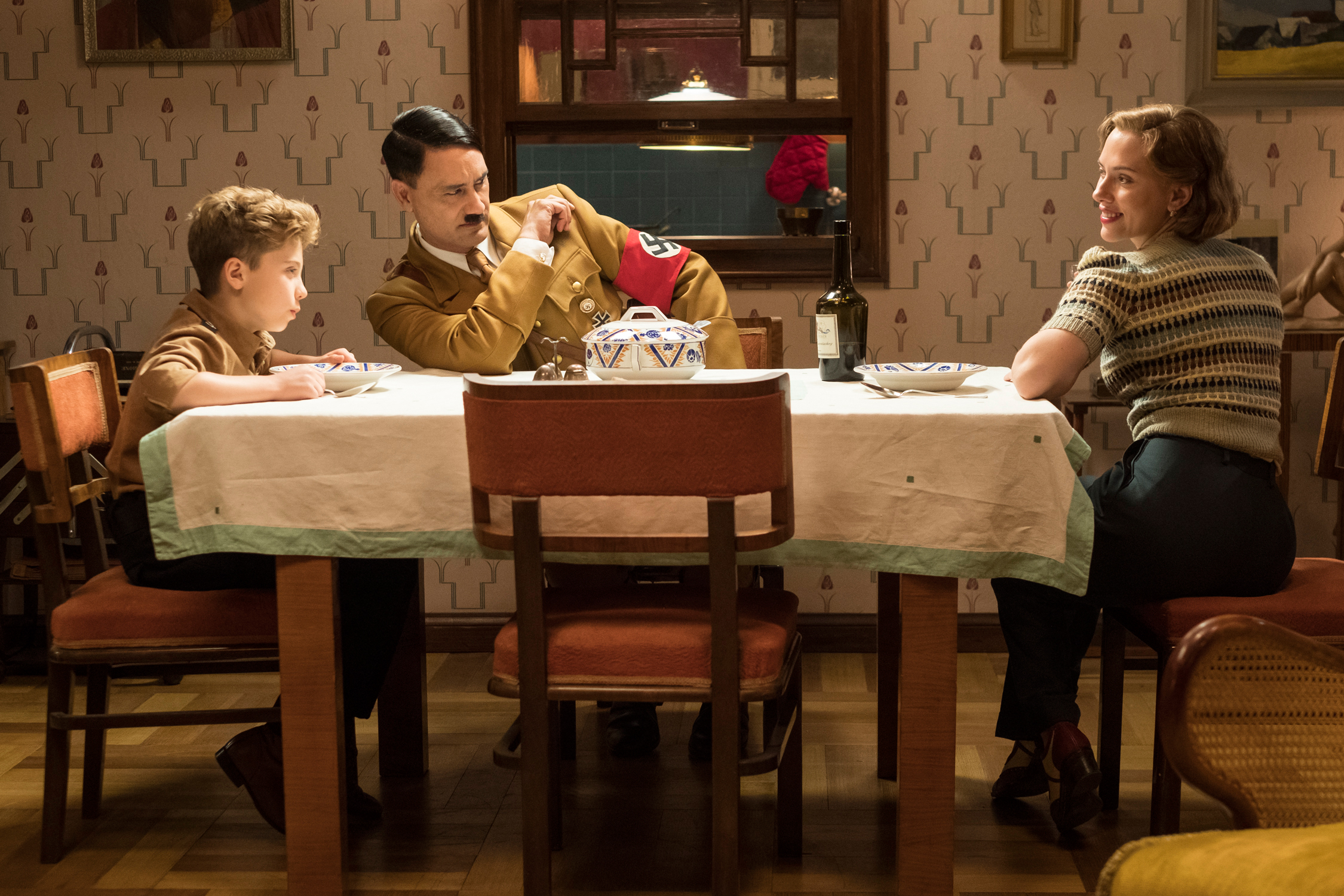 Taika Waititi's Hitler sits at a table with Jojo and his Rosie (Scarlett Johansson)