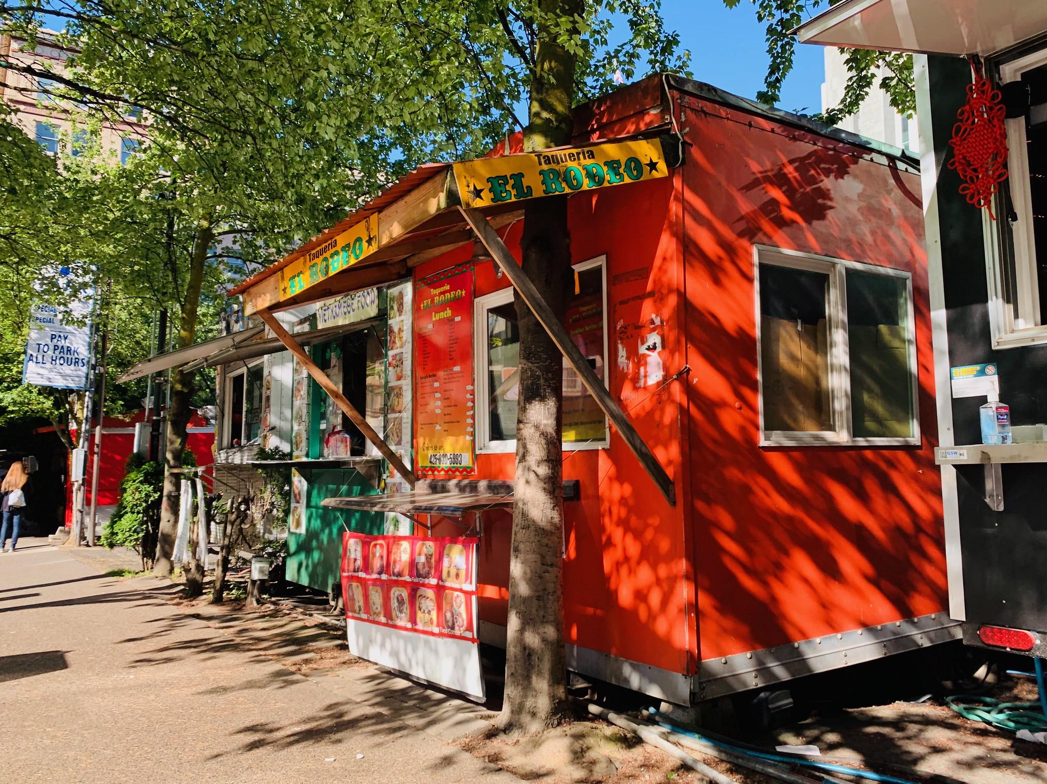 Bright red food cart Taqueria El Rodeo in the sun