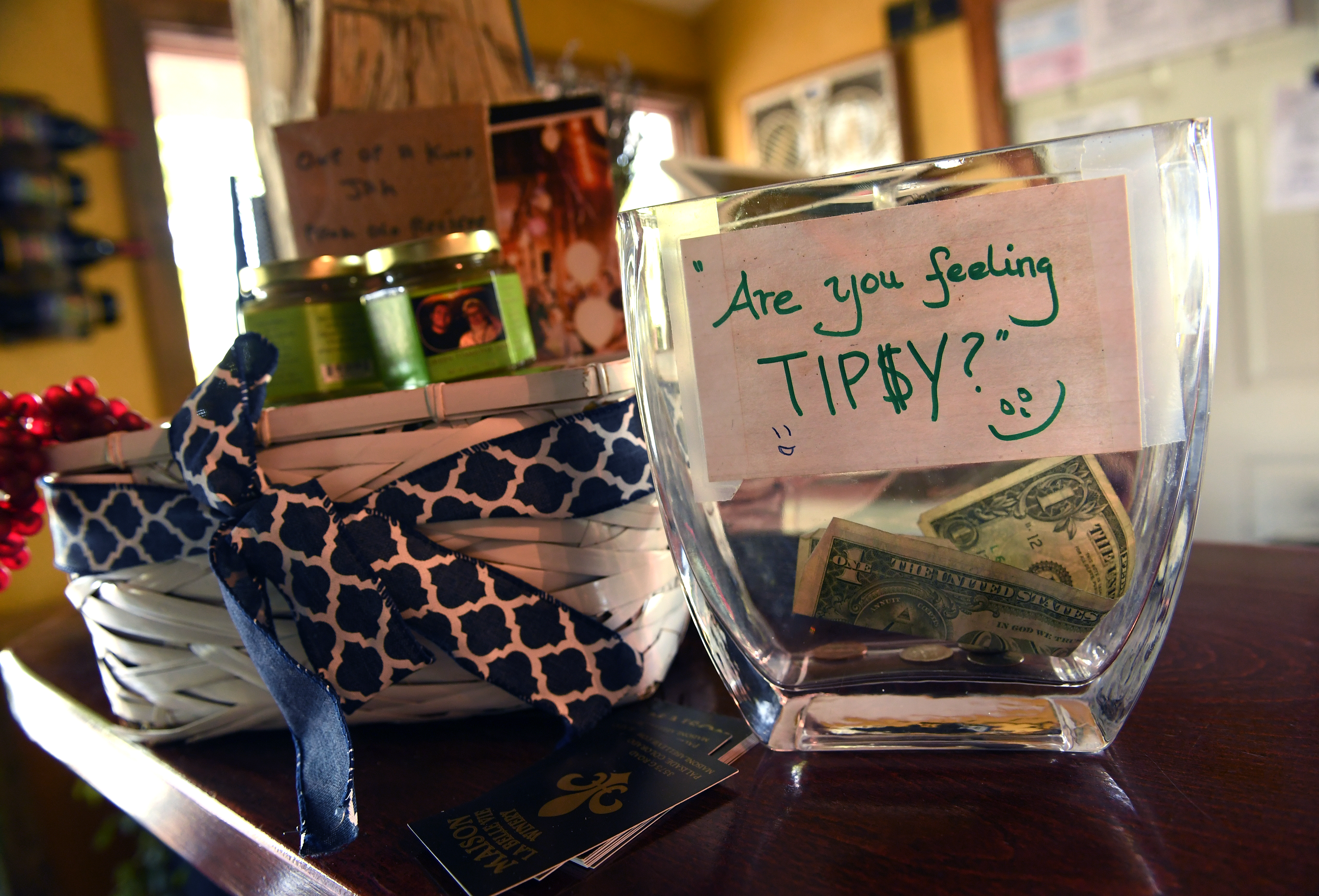 "A tip jar on a store counter with a sign that reads, ""Are you feeling tipsy?"""