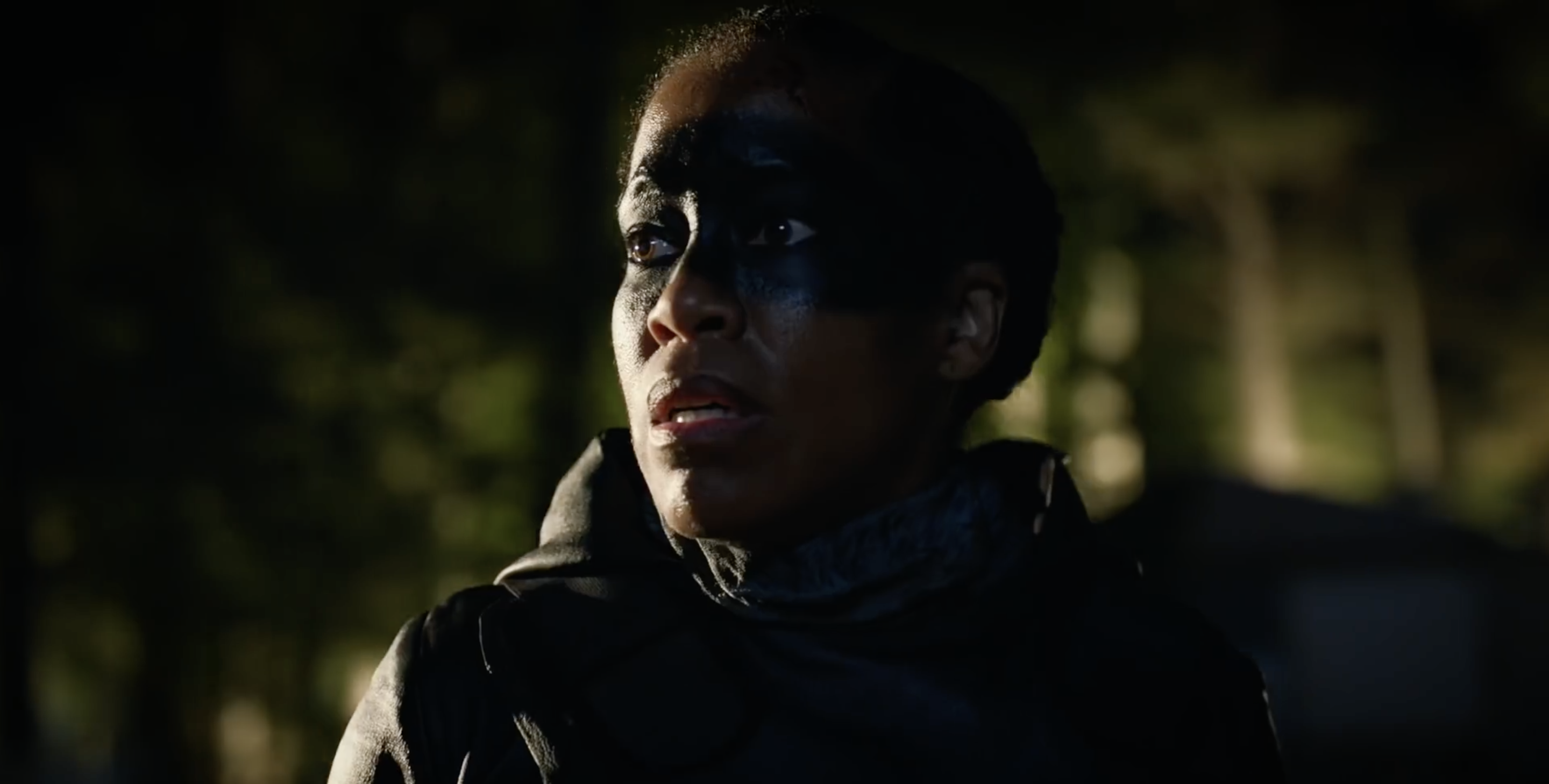 Angela Abraham (Regina King), with dark paint over her eyes, watches chaos unfold.