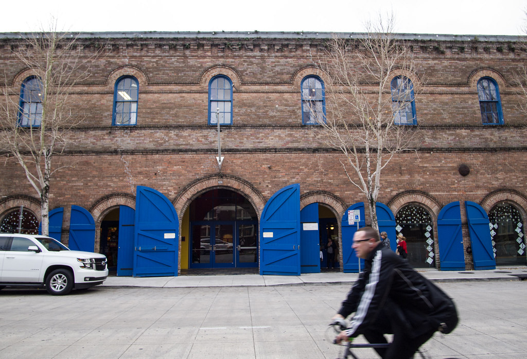 A bicyclist speeds past a brick warehouse with bright-blue doors on Julia Street in New Orleans