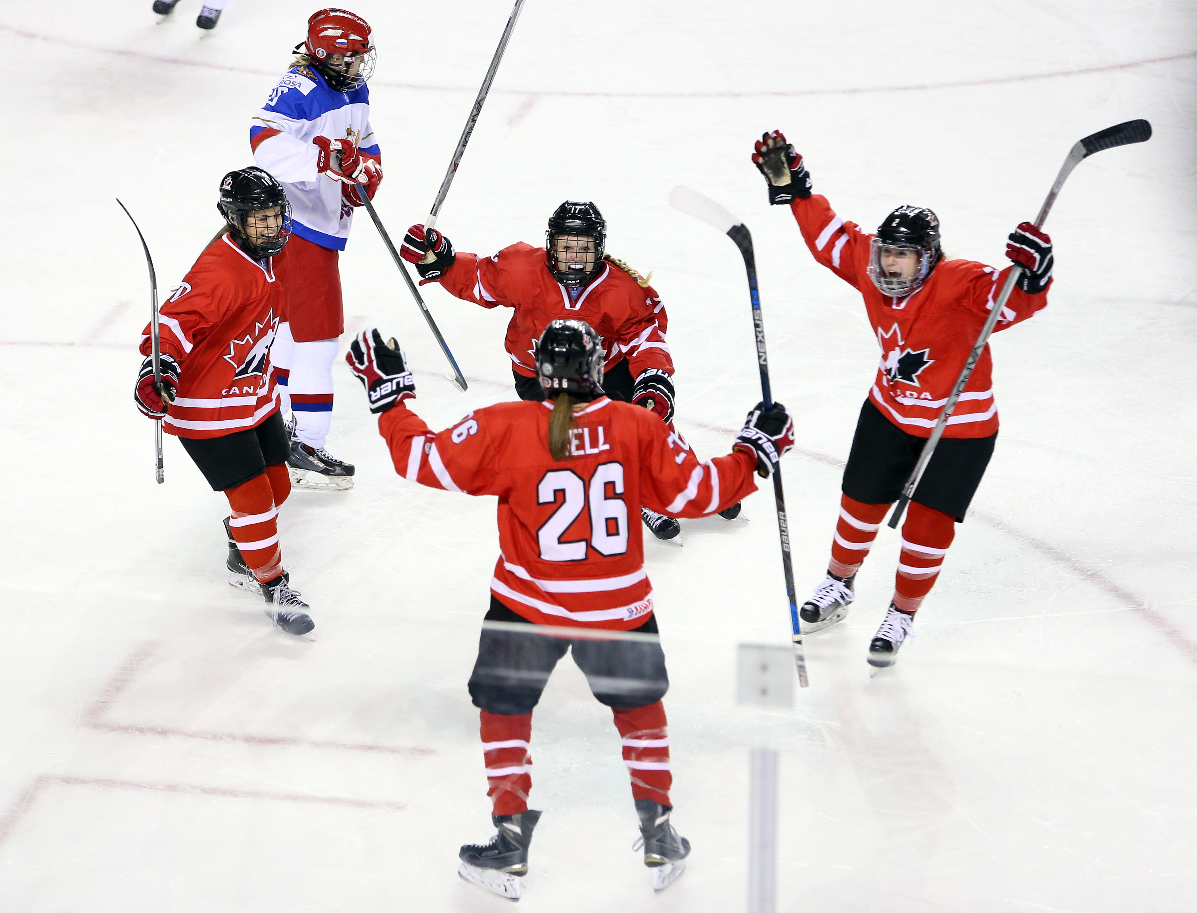 Kristin O'Neill #10, Emma Maltais #17 and Codie Cross #2 of Team Canada celebrate a goal by teammate Ashton Bell #26 in a semifinal game against Team Russia during the 2016 IIHF U18 Women's World Championships at the Meridian Centre on January 14, 2