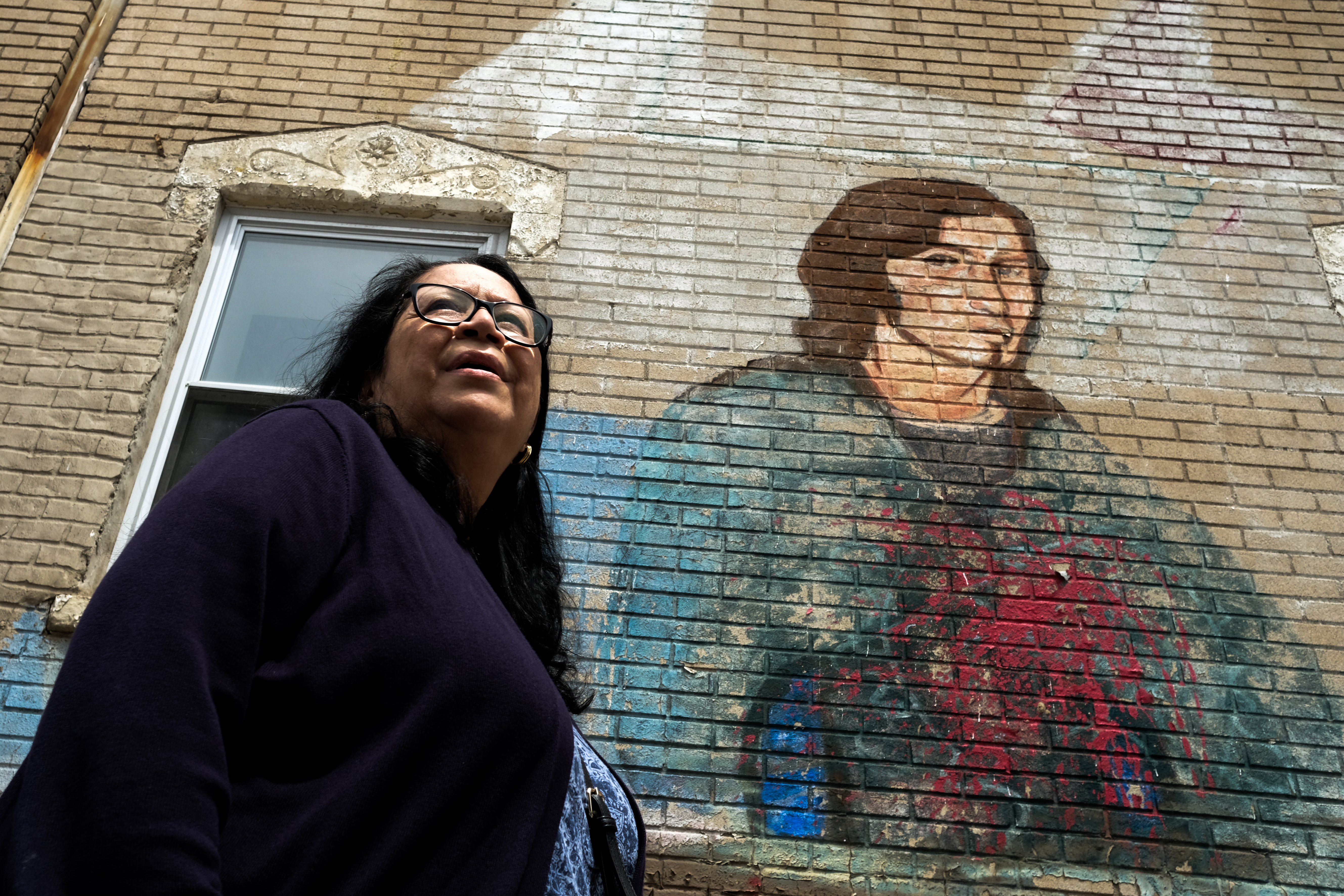 "Annabelle Gonzales-Falcon in front of a mural in Pilsen depicting her brother David ""Boogie"" Gonzales."