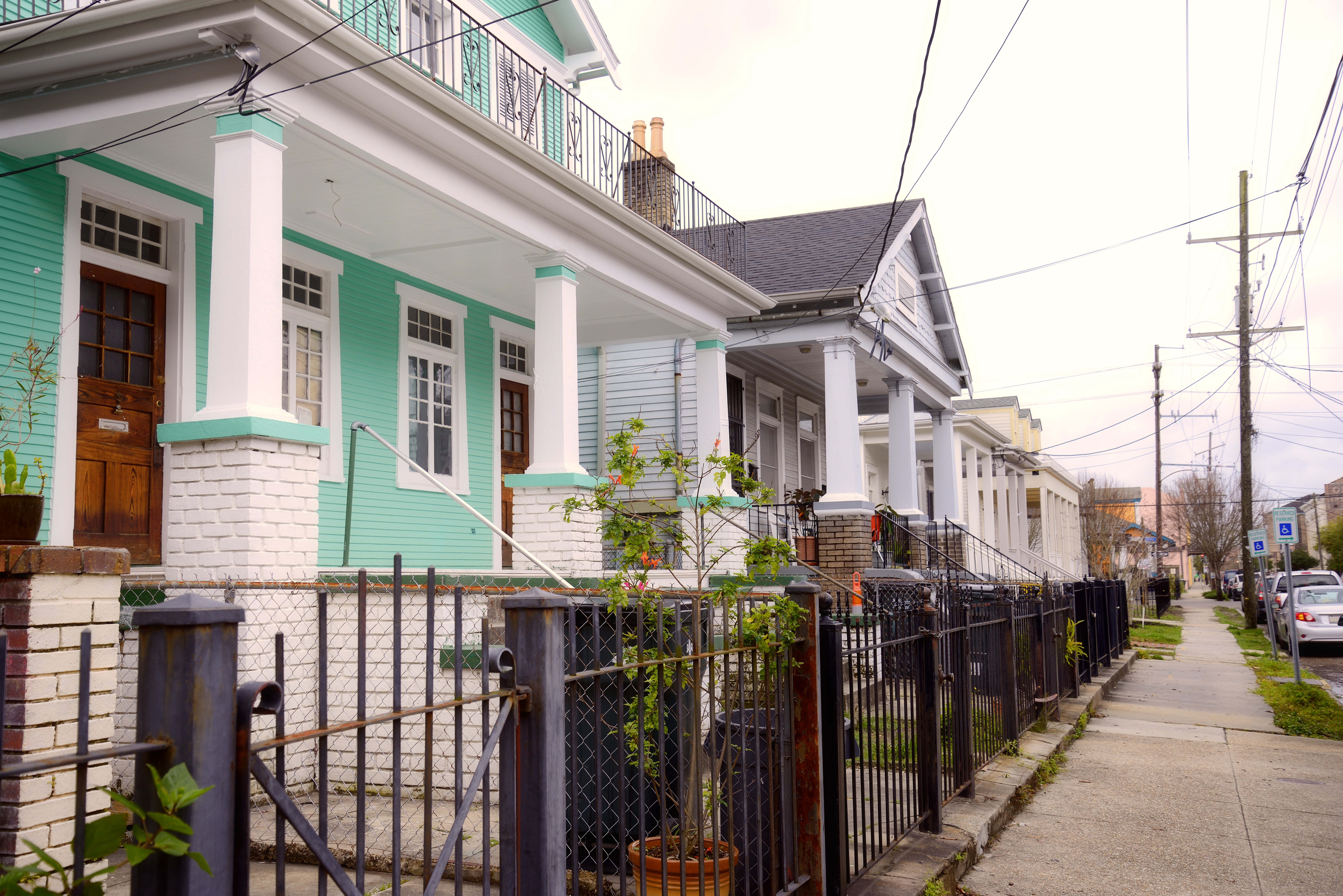 A row of New Orleans-style doubles on the left side of the street include a mint green home with white columns and black iron fence in front of a sidewalk