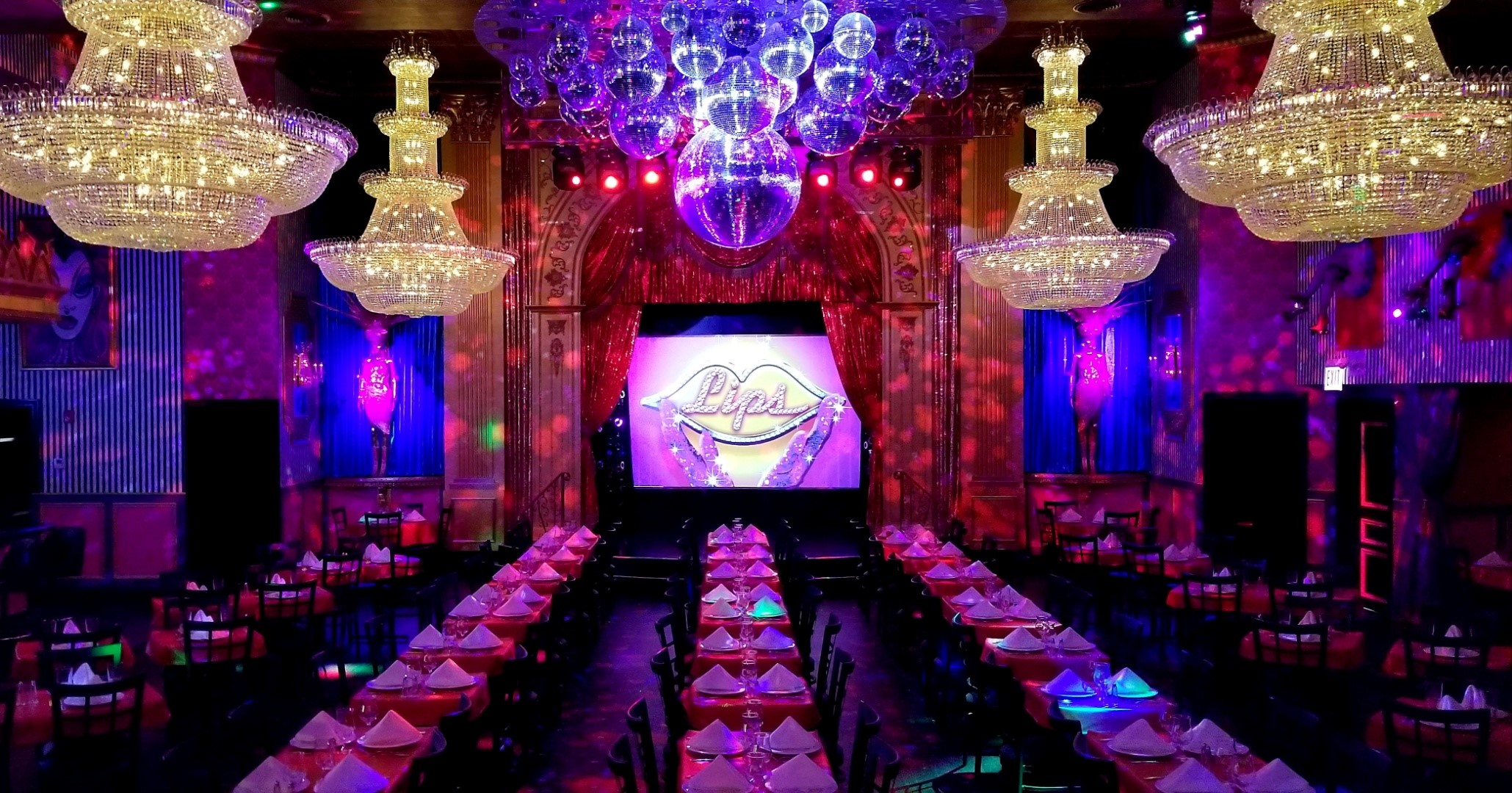 Brightly colored tables and chairs fill a large dark room with a stage in the rear.