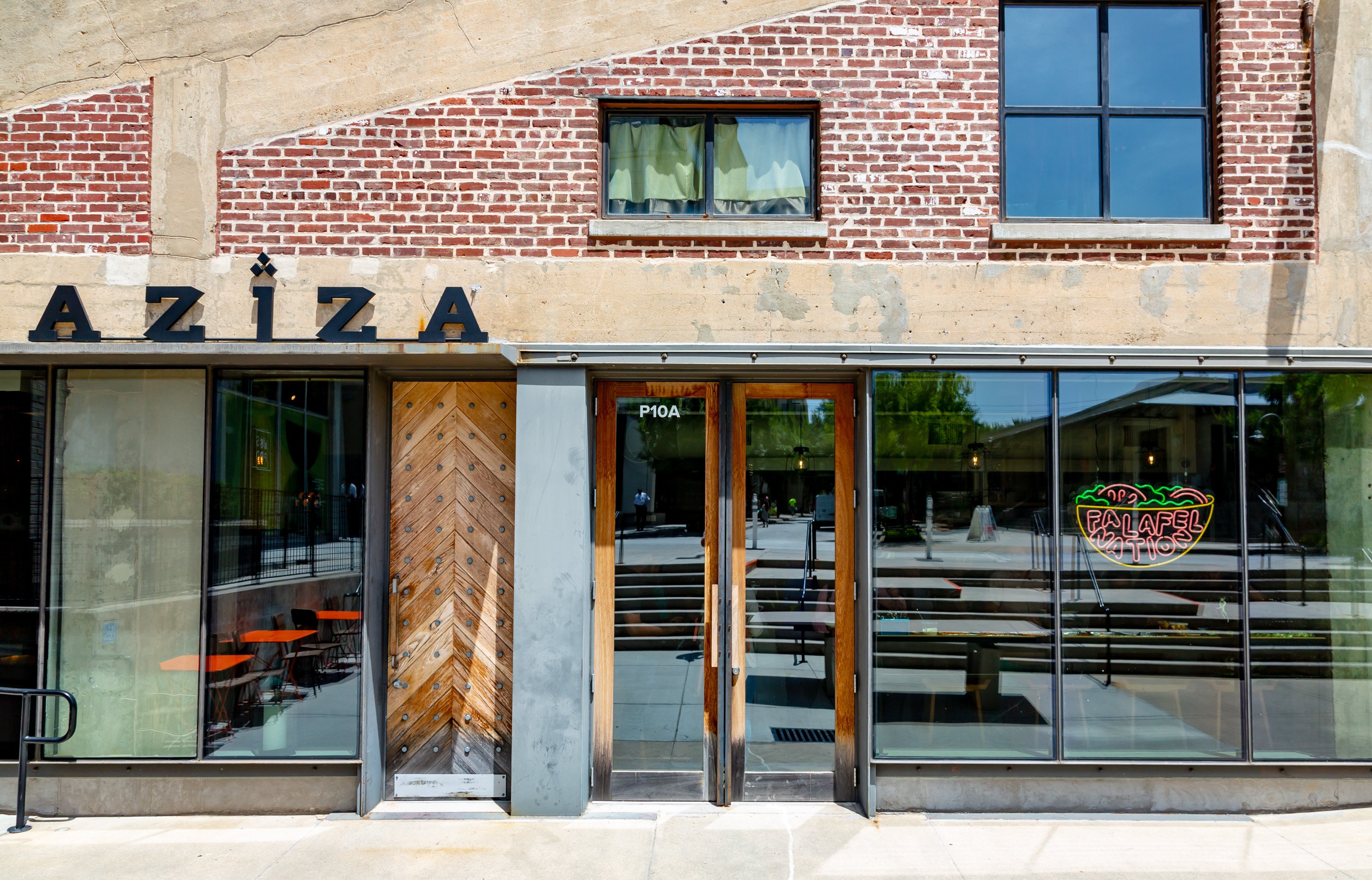 The front doors and signs for restaurants Aziza and Falafel Nation at Westside Provisions District