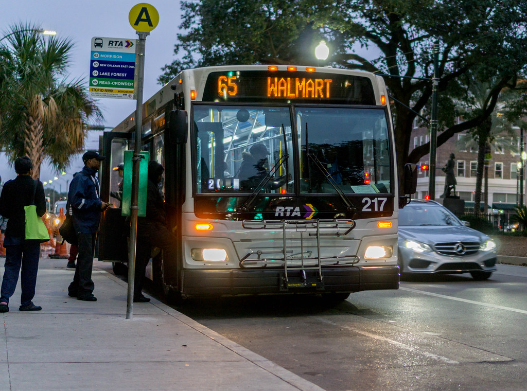 A New Orleans RTA bus picks up passengers at dusk