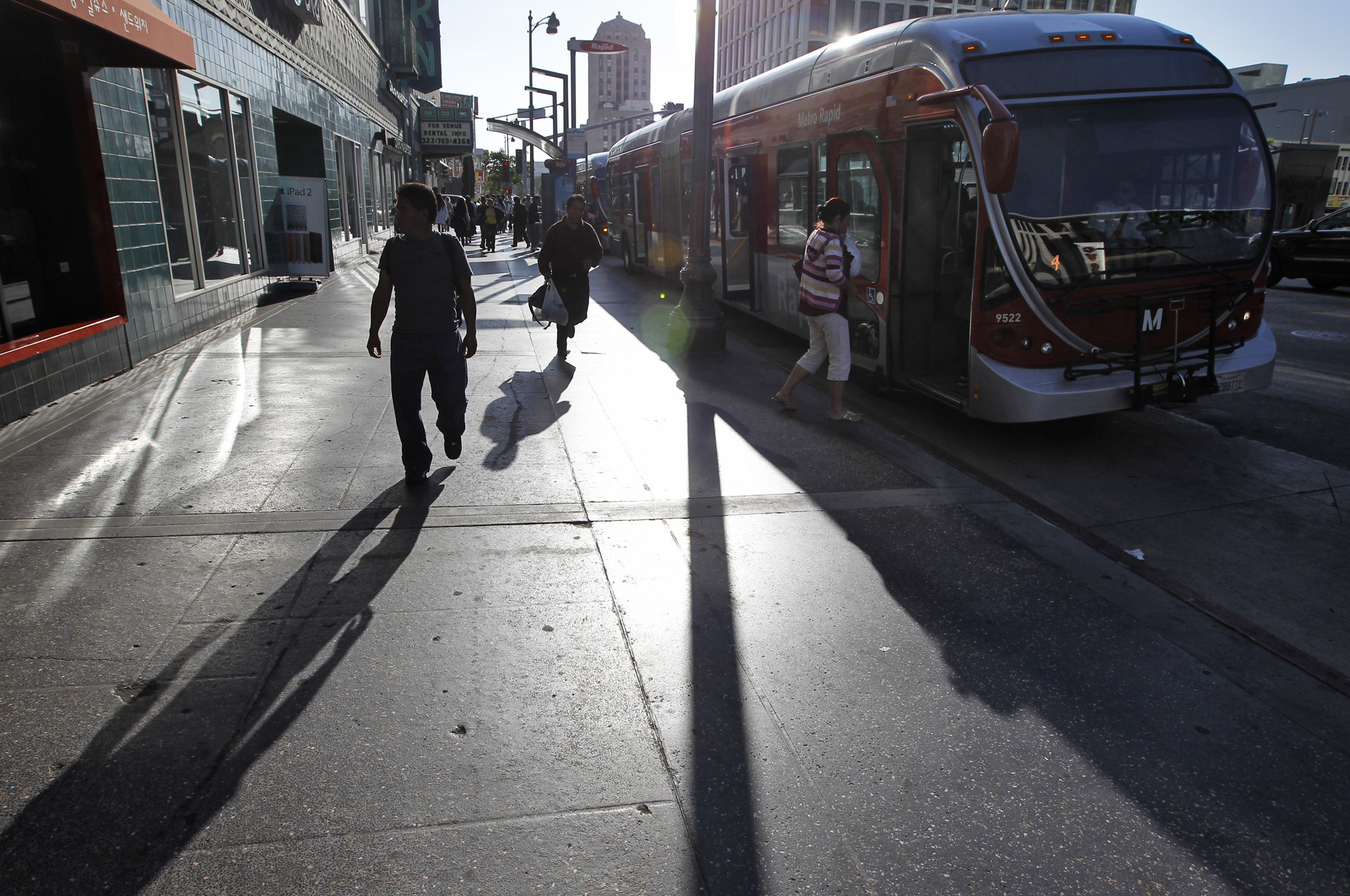 Riders step off an orange Metro bus on Wilshire Boulevard at a stop with no shade. The sun's rays are visible.