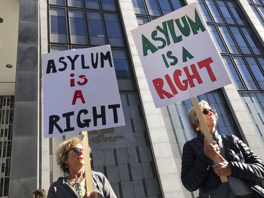 """Protestors hold signs that read """" Asylum is a Right"""" outside of the San Francisco Federal Courthouse on Wednesday, July 24, 2019 in San Francisco, Calif."""
