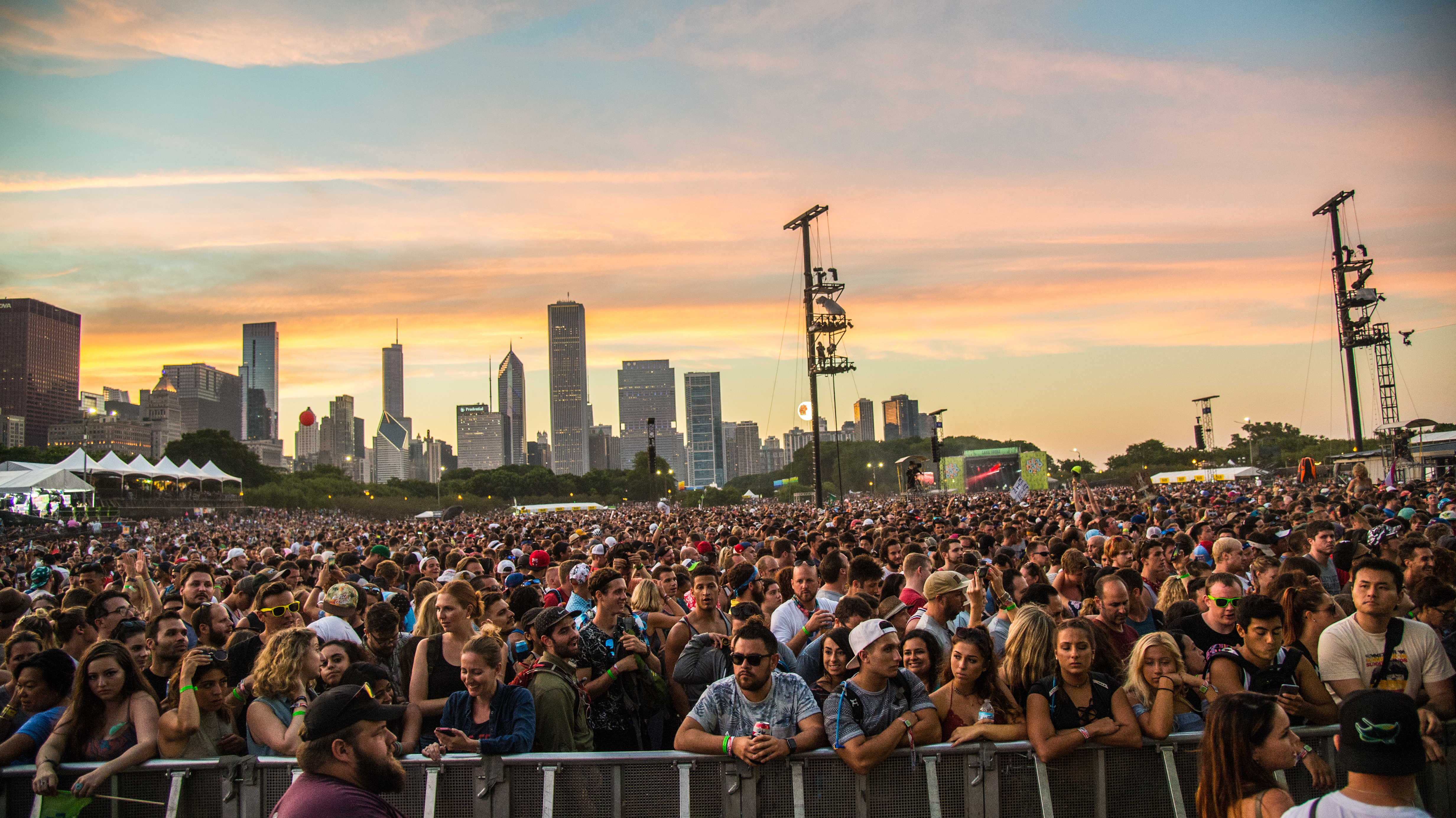 A Lollapalooza crowd looks at a massive stage behind the photographer. Sunset sky and Chicago skyscrapers in the back.