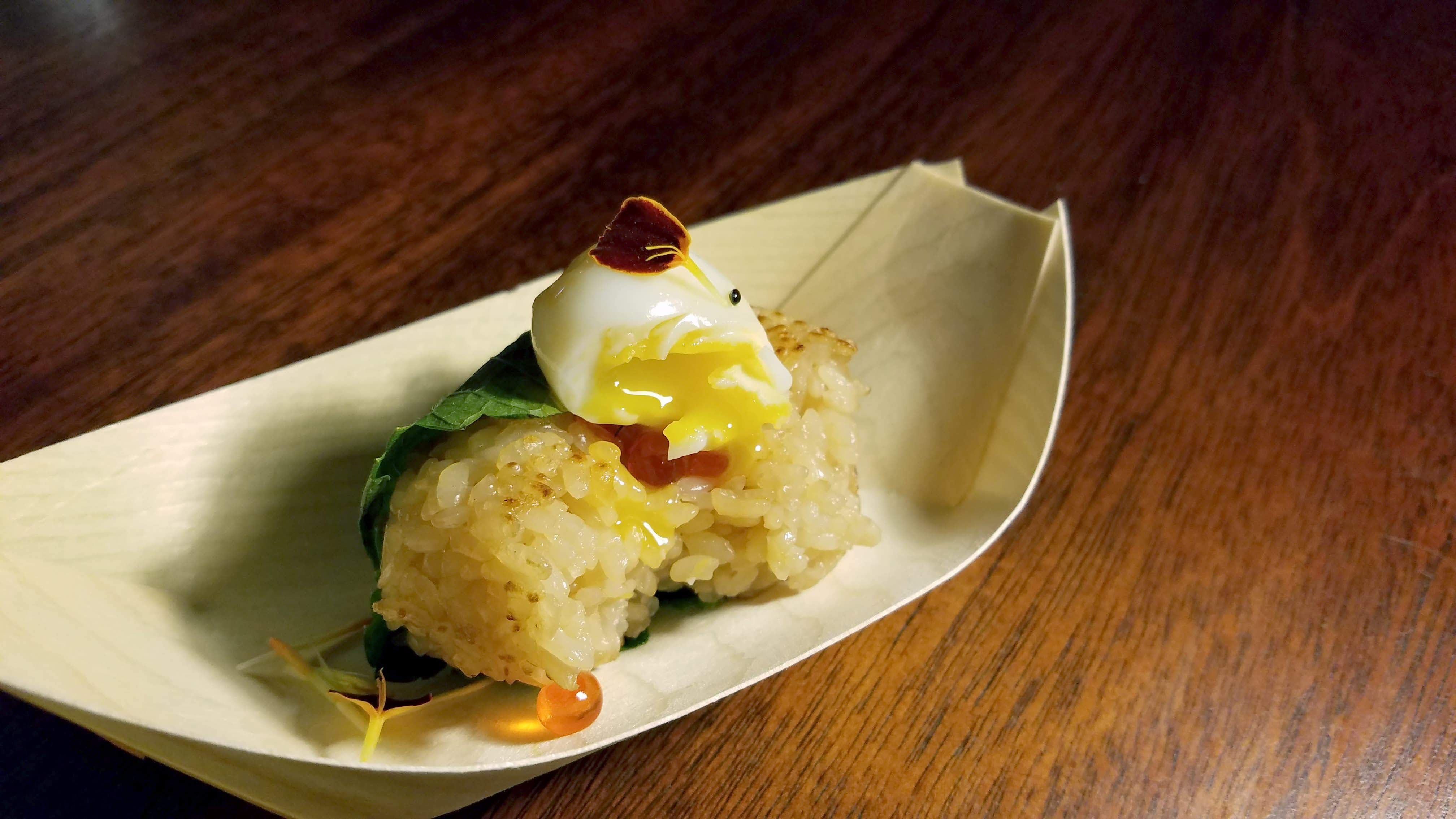Tanuki's quail egg onigiri —a rice ball topped with an oozing quail egg and some edible flowers and other garnishes
