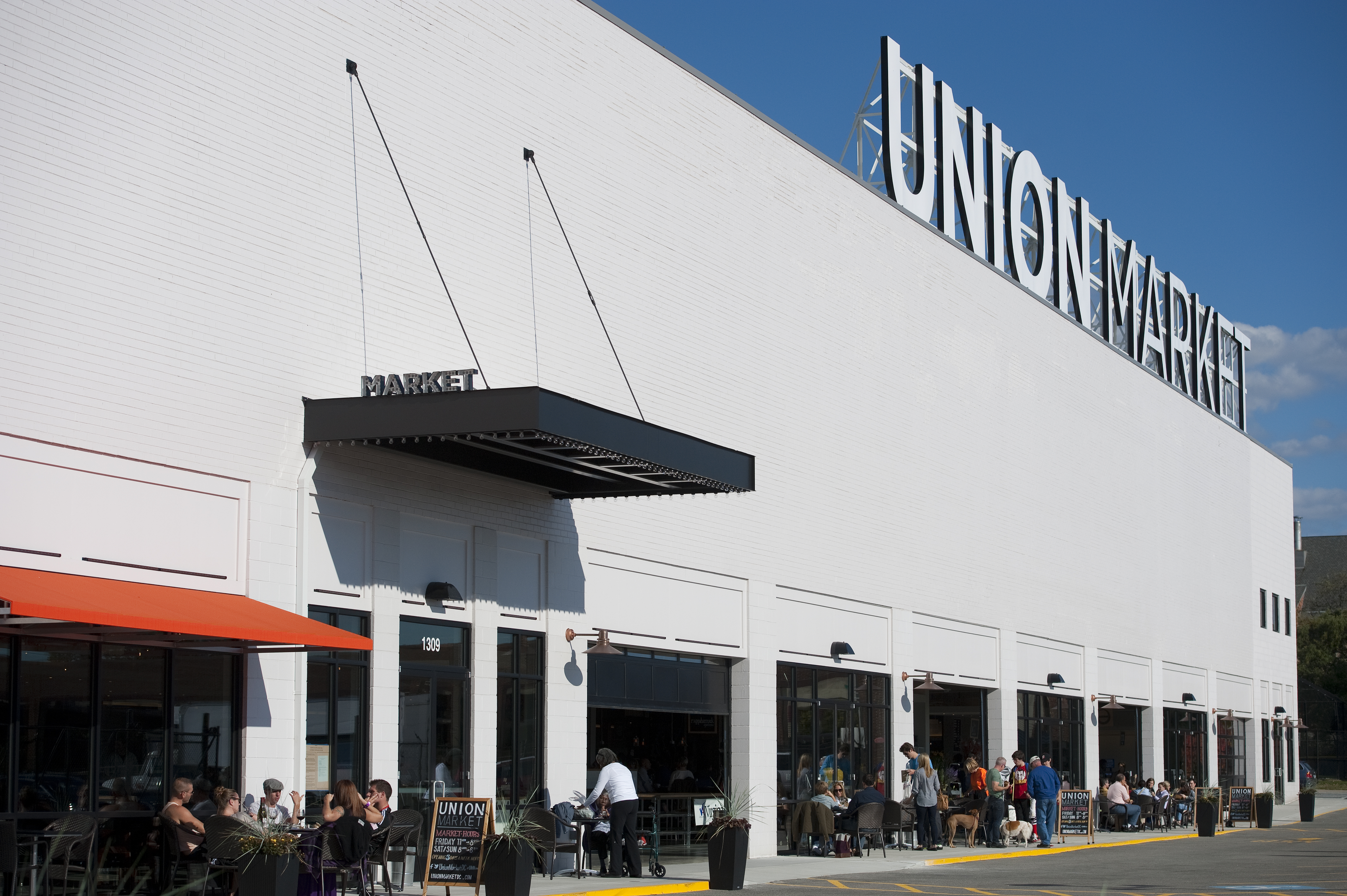 Union Market, a wide warehouse-like building with groups of people sitting out front.