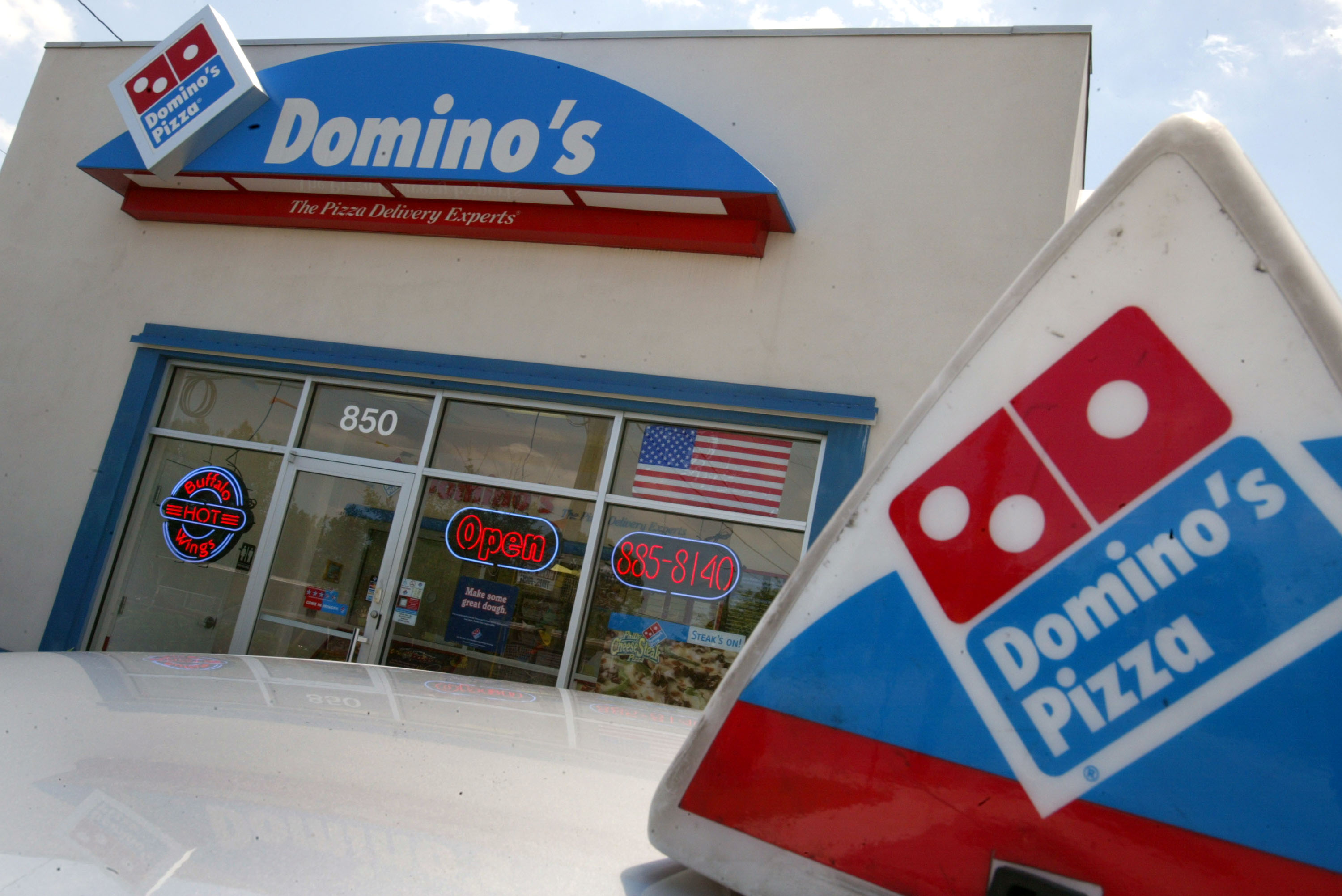 A mid-2000s Domino's sign on a blue curved awning on a white building with blue framed windows. In the foreground there's a Domino's delivery car with a triangular Domino's sign on top.