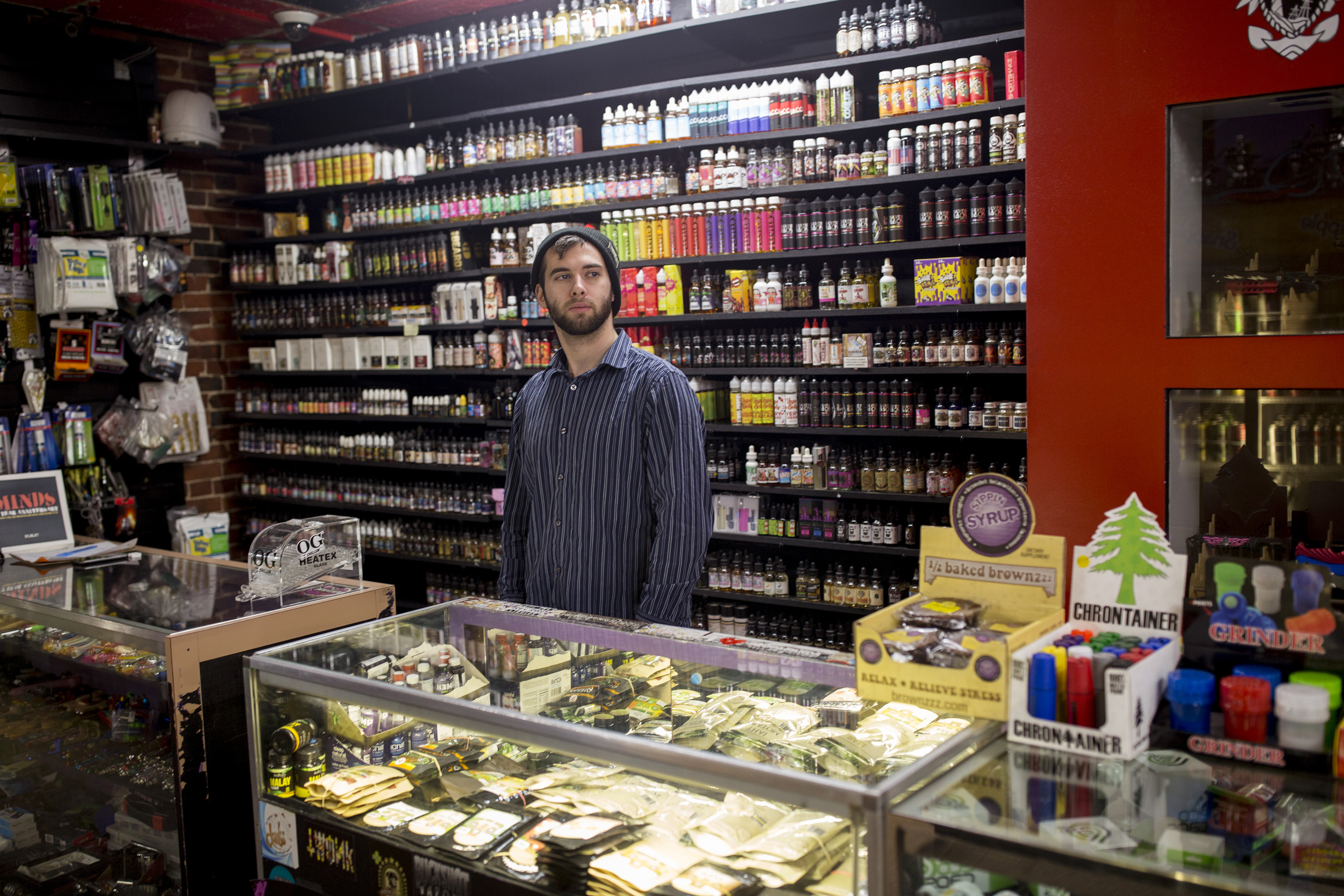 a man standing in vape shop with crowded shelves of e-liquid behind a glass counter