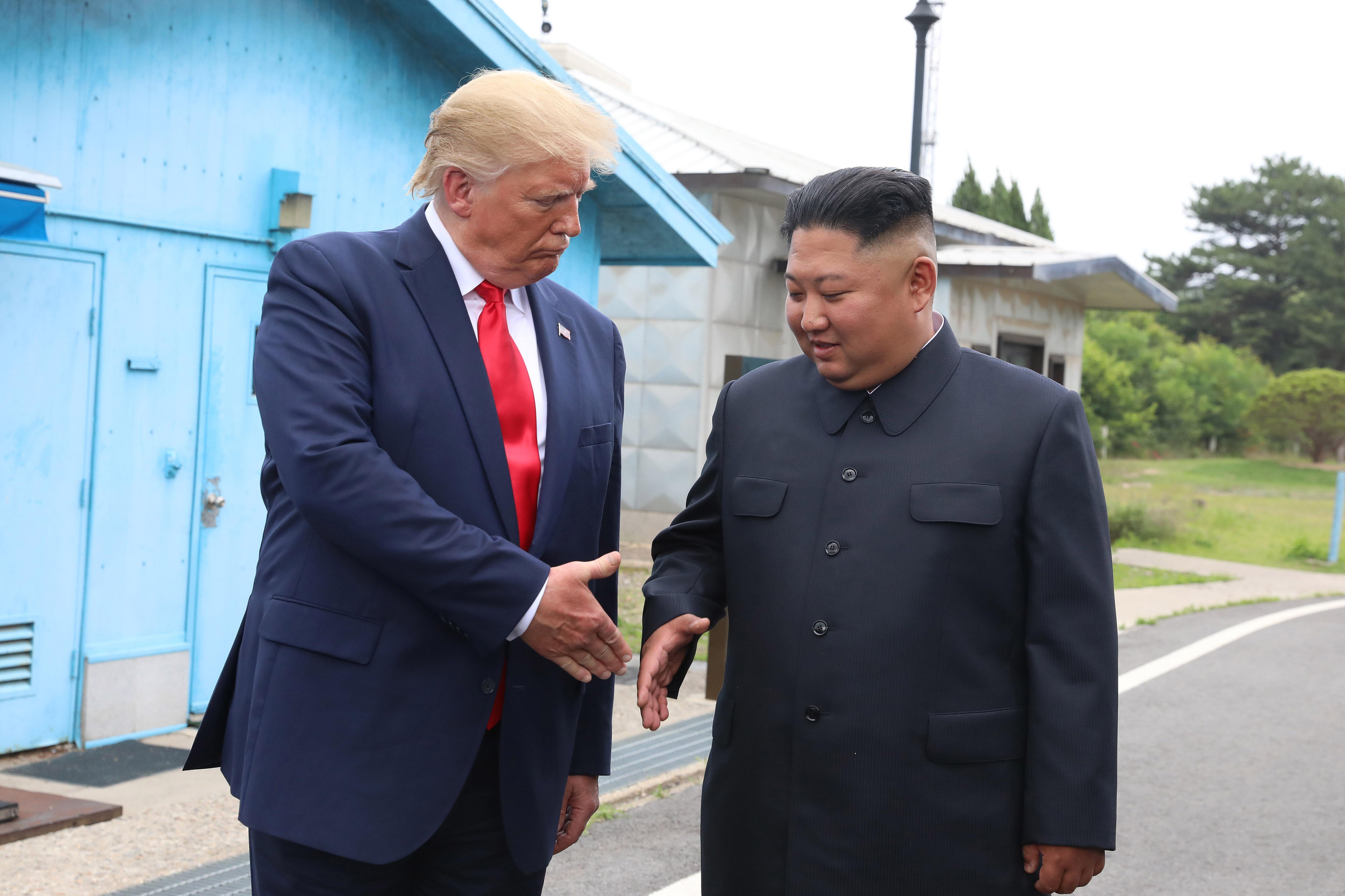 President Trump and Kim Jong Un starting to shake hands.