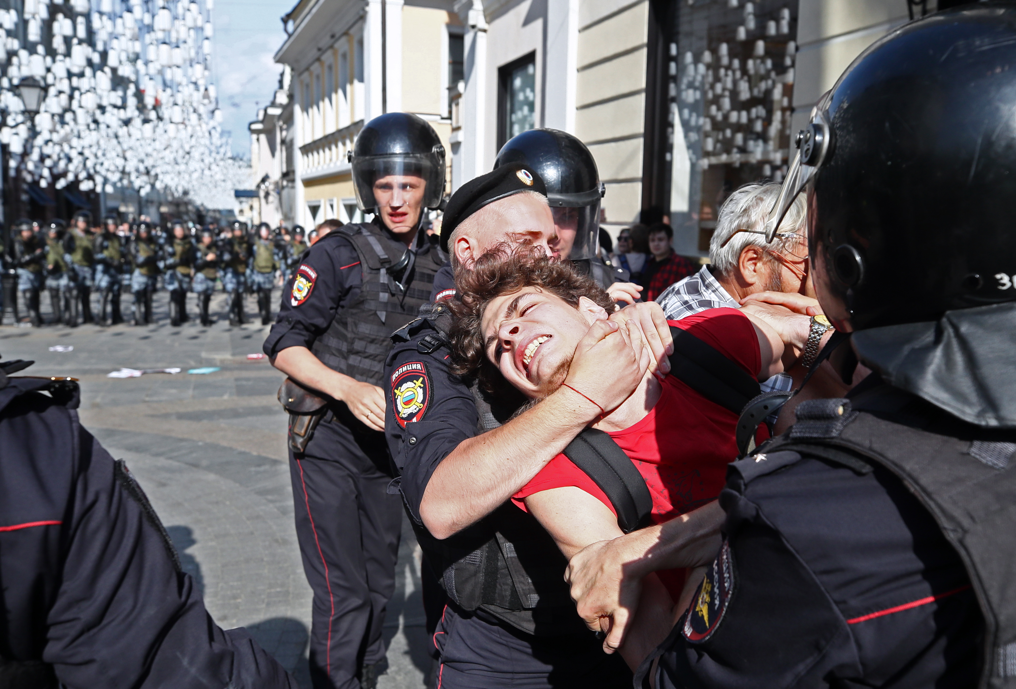 A Russian man struggles as he is arrested by two police officers, one of whom has him in a chokehold.