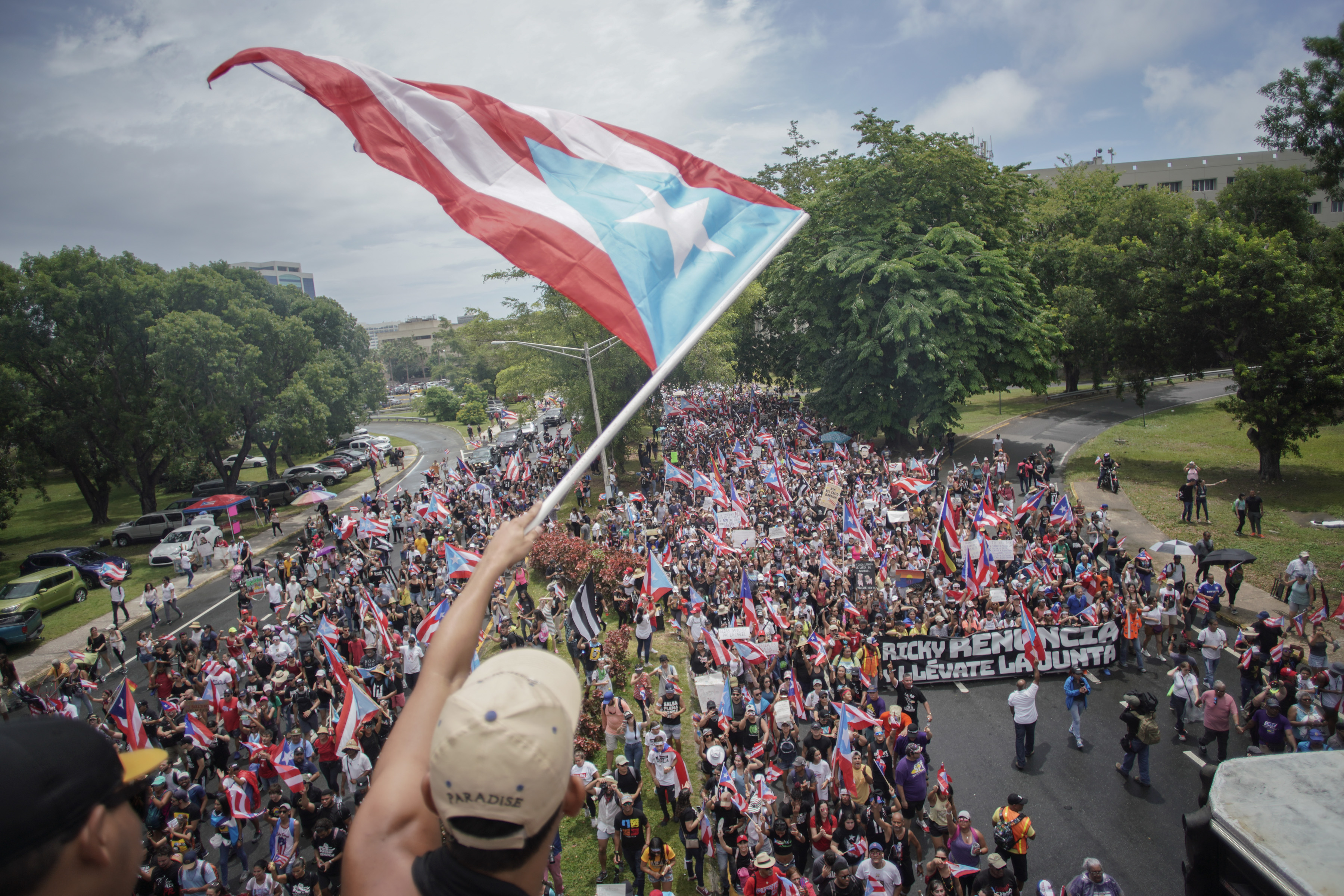 A man waves the Puerto Rican flag in front of a group of protesters.