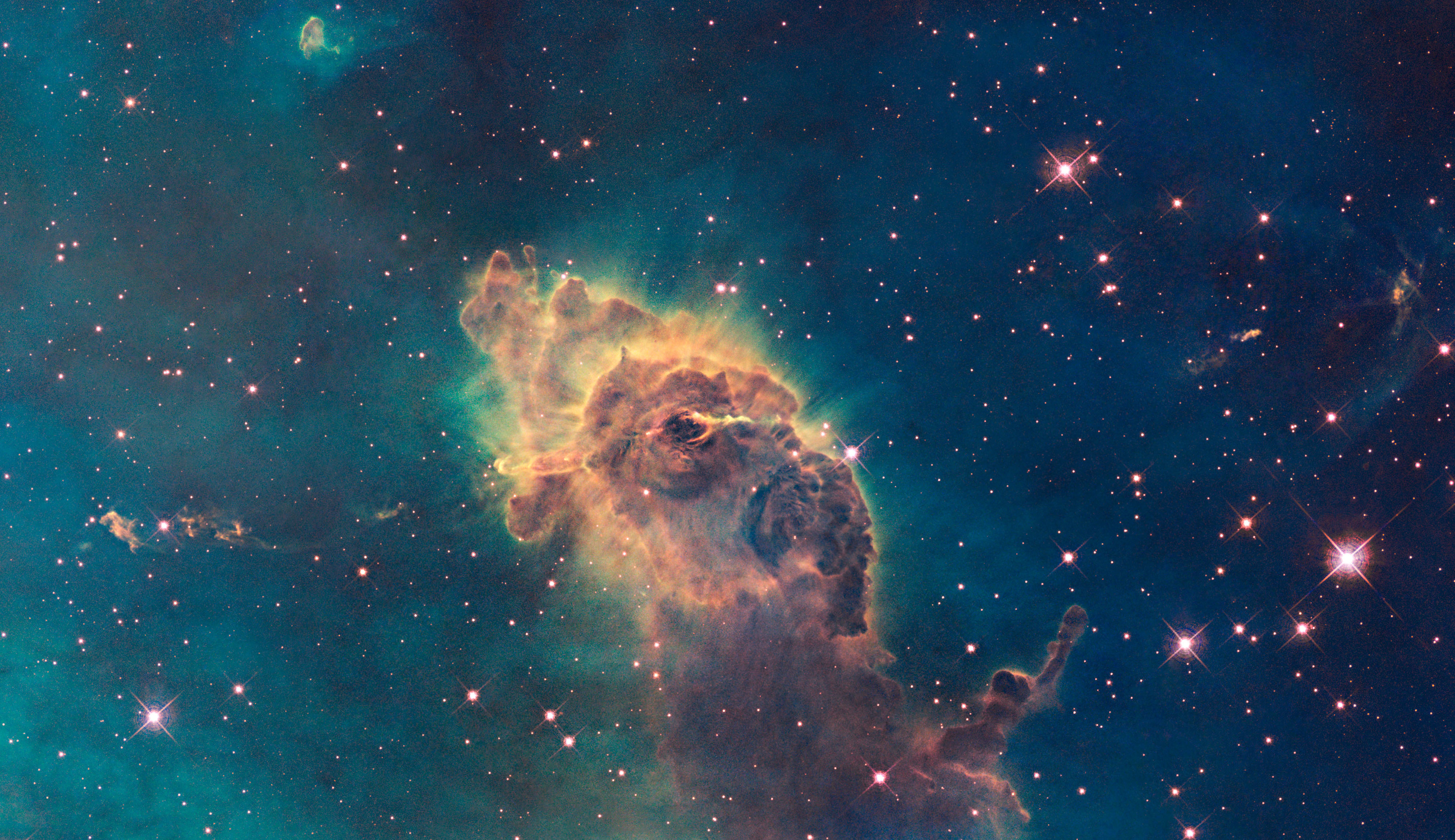 This image made by the NASA/ESA Hubble Space Telescope shows the tip of the three-light-year-long pillar in a stellar nursery called the Carina Nebula, located 7500 light-years away from the Earth.