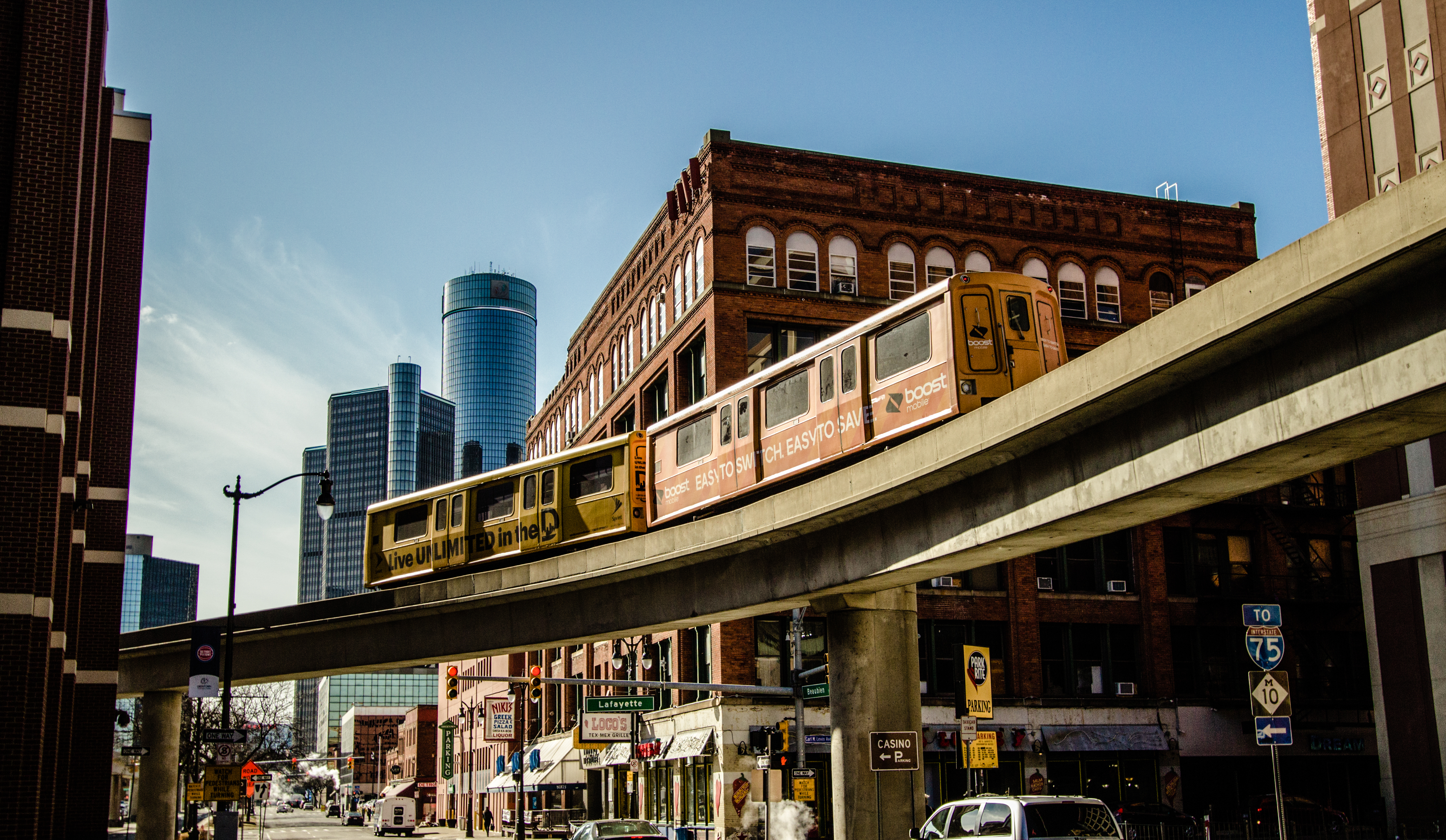 Detroit's elevated people mover moves diagonally across a busy downtown street.