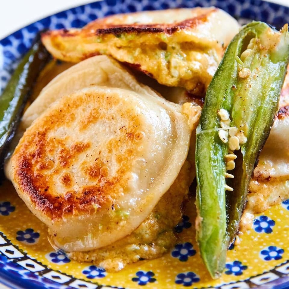 A pile of pan fried pierogi with a fried jalapeno sliced in half on a decorative canary blue and yellow Polish plate.