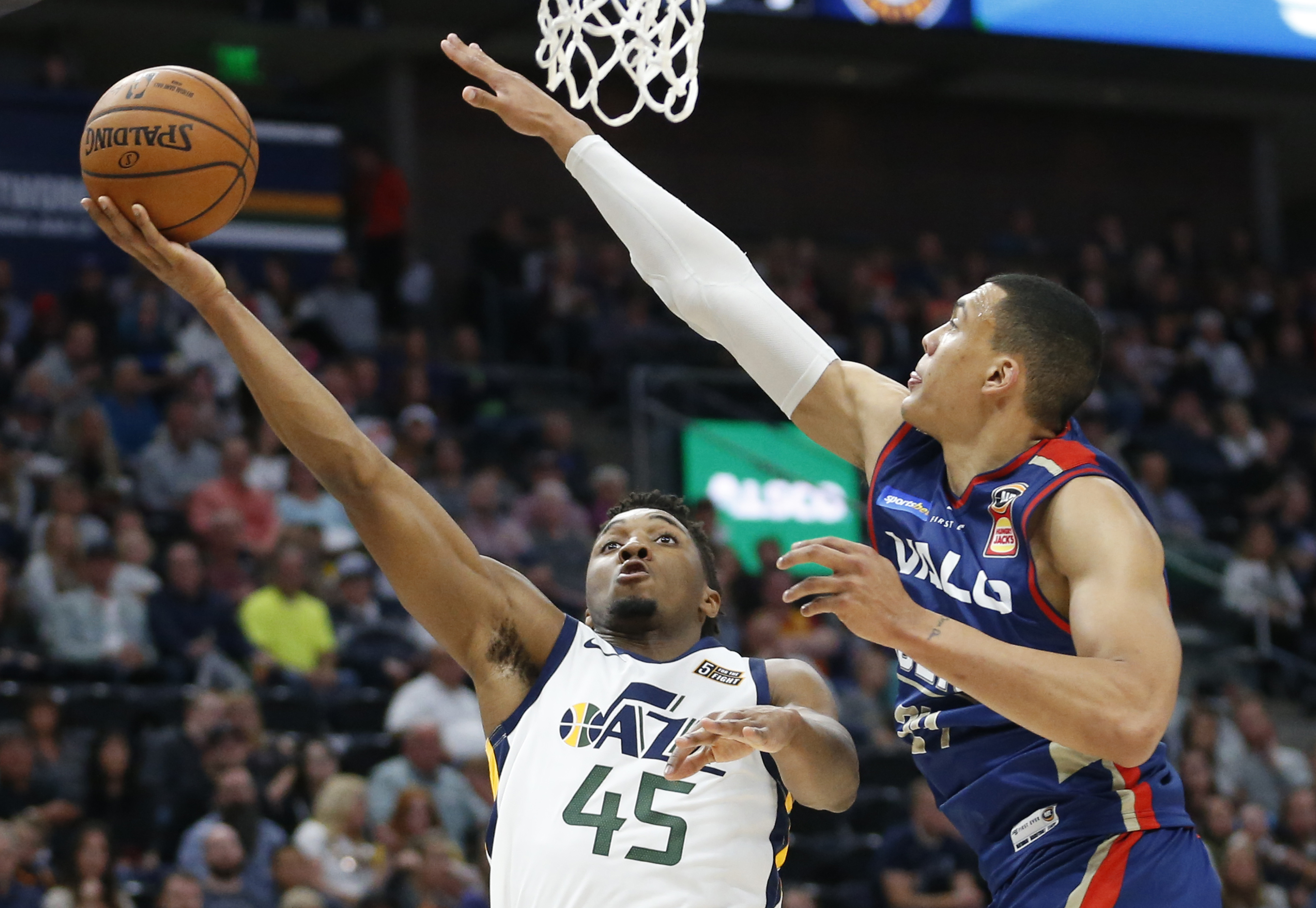 Utah Jazz guard Donovan Mitchell (45) lays the ball up as Adelaide 36ers forward Jake Wiley, right, defends during the first half during an NBA exhibition basketball game Friday, Oct. 5, 2018, in Salt Lake City. (AP Photo/Rick Bowmer)