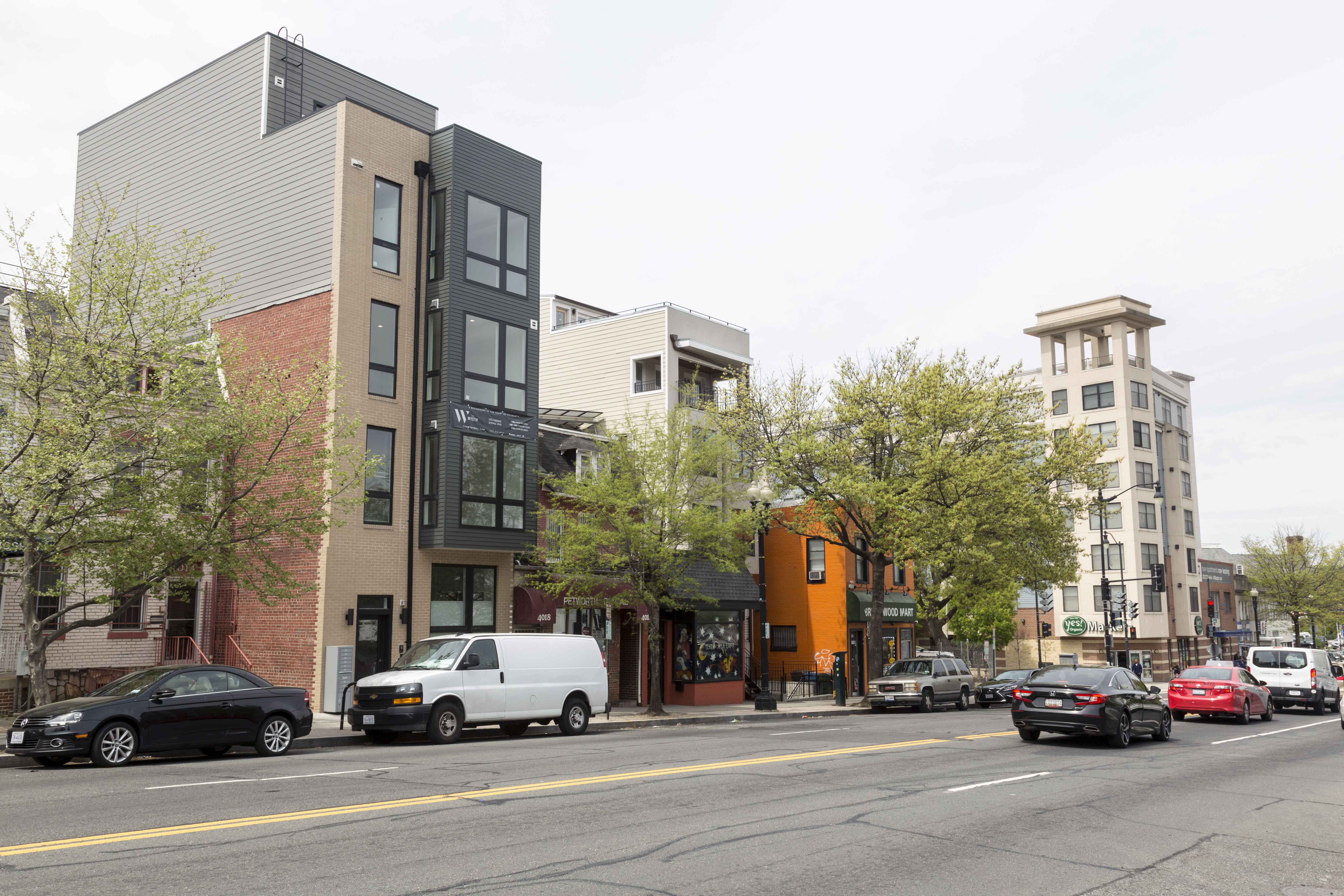 A row of buildings on Georgia Avenue NW, ranging in height from two to six stories, with the street in the foreground. Several cars are parked or are being drive on the street.