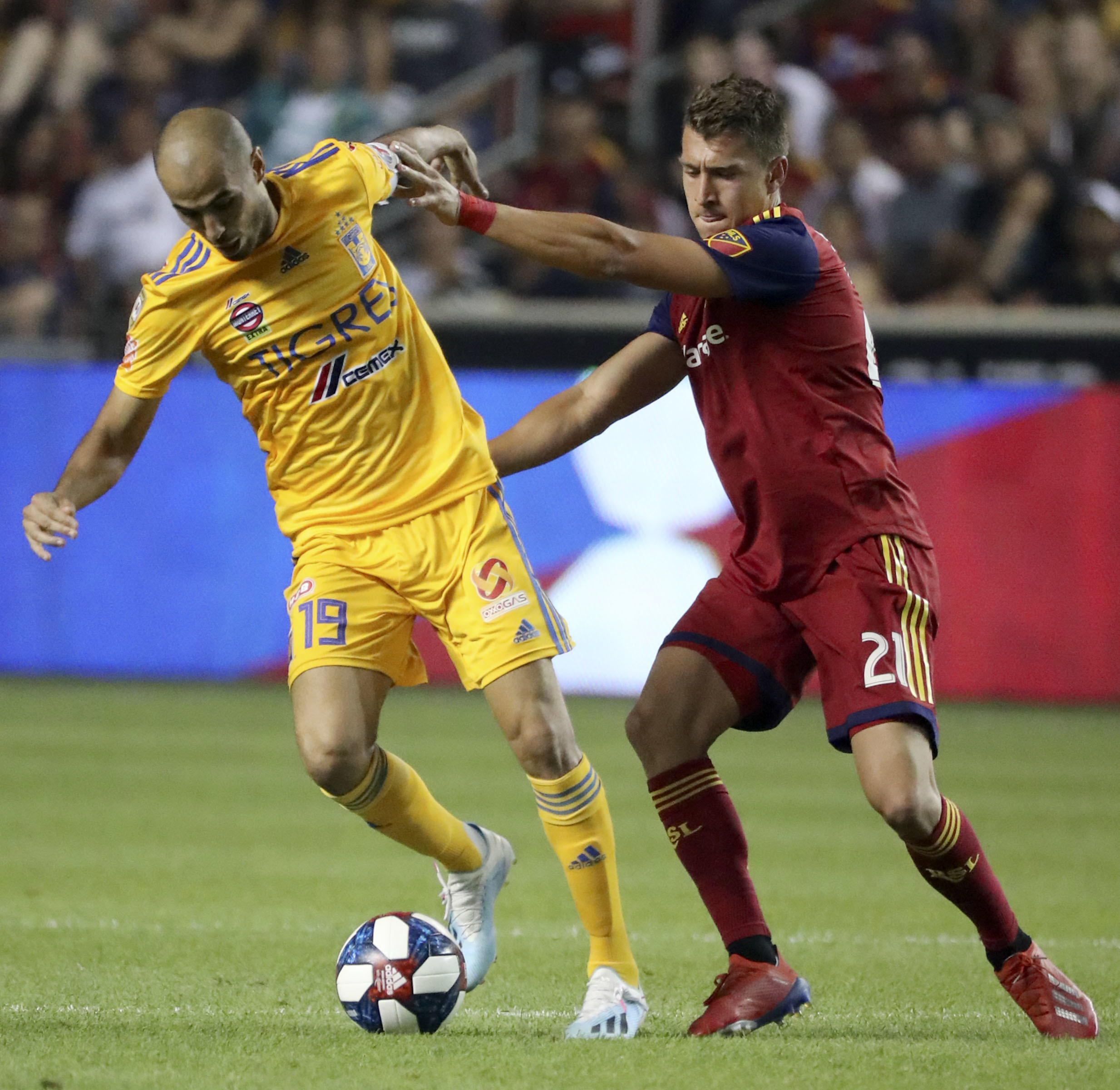 Real Salt Lake forward Tate Schmitt (21) pushes UANL Tigres midfielder Guido Pizarro (19) as he kicks the ball during a Leagues Cup soccer match at Rio Tinto Stadium in Sandy on Wednesday, July 24, 2019. Real Salt Lake lost 0-1.