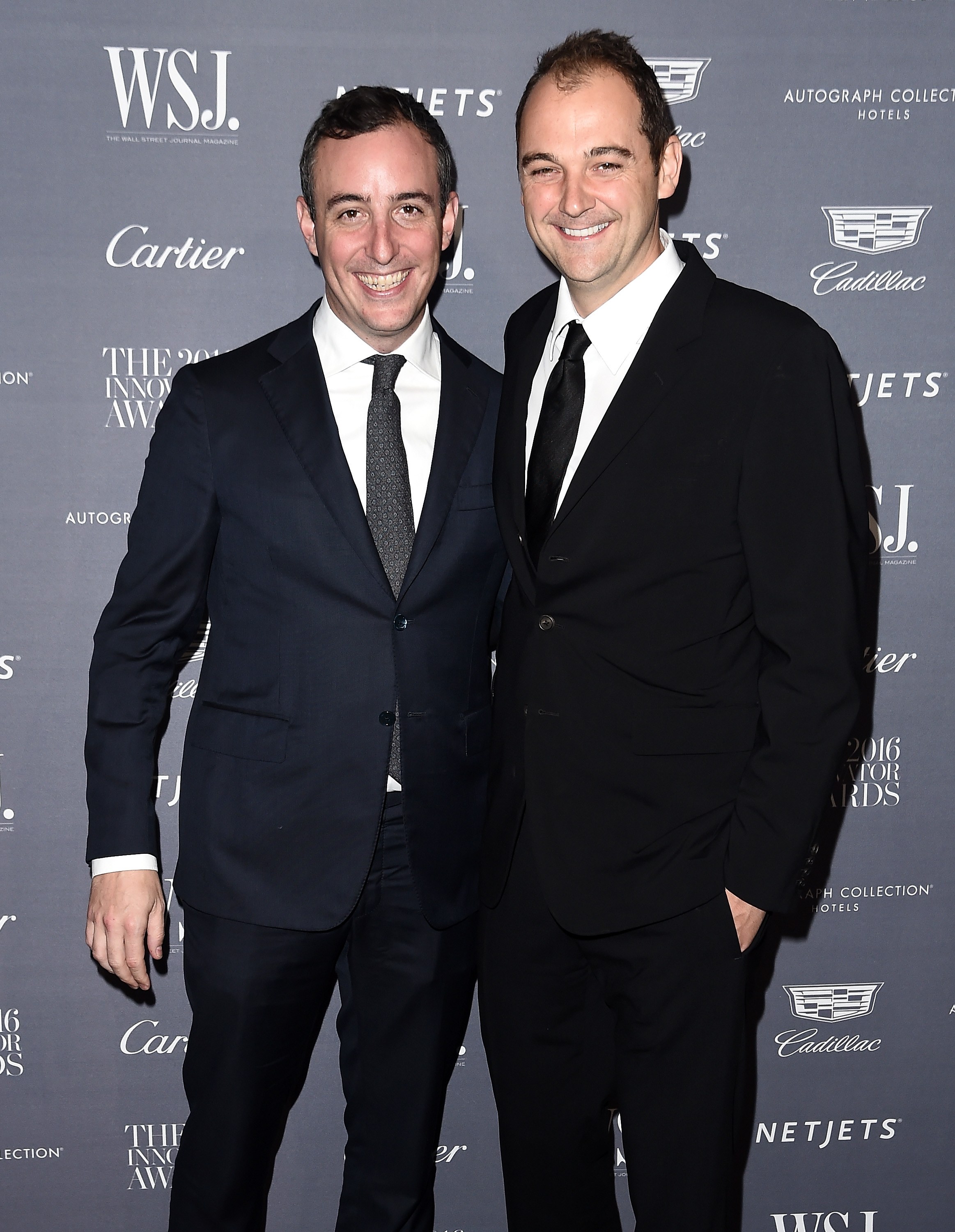 Eleven Madison Park's Daniel Humm and Will Guidara, wearing suits and smiling, standing in front of a step and repeat sign at a party