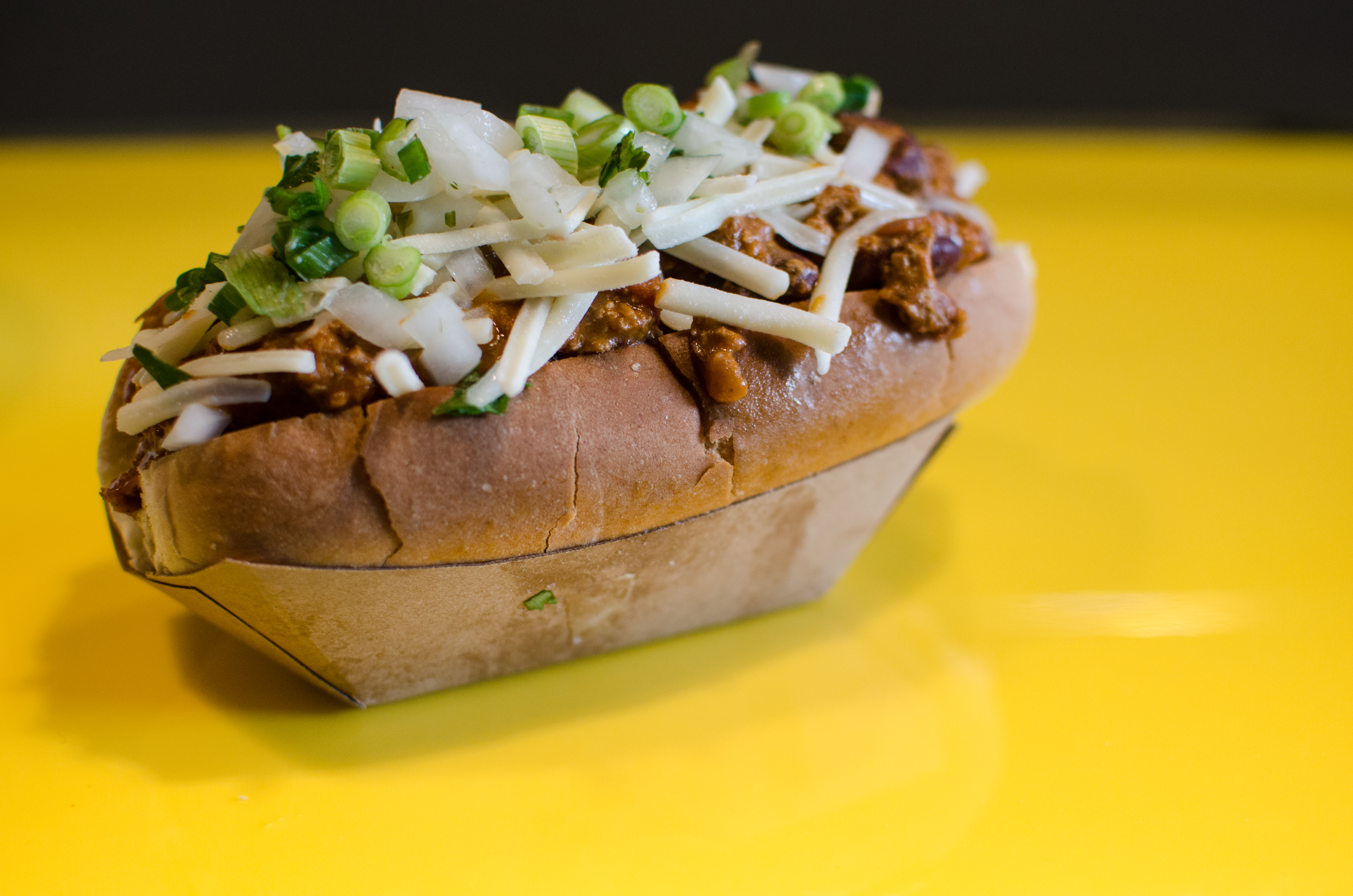 At Saus's all-vegetarian location in Somerville, the chili-cheese dog, pictured here on a bright yellow counter, is made with Beyond sausage